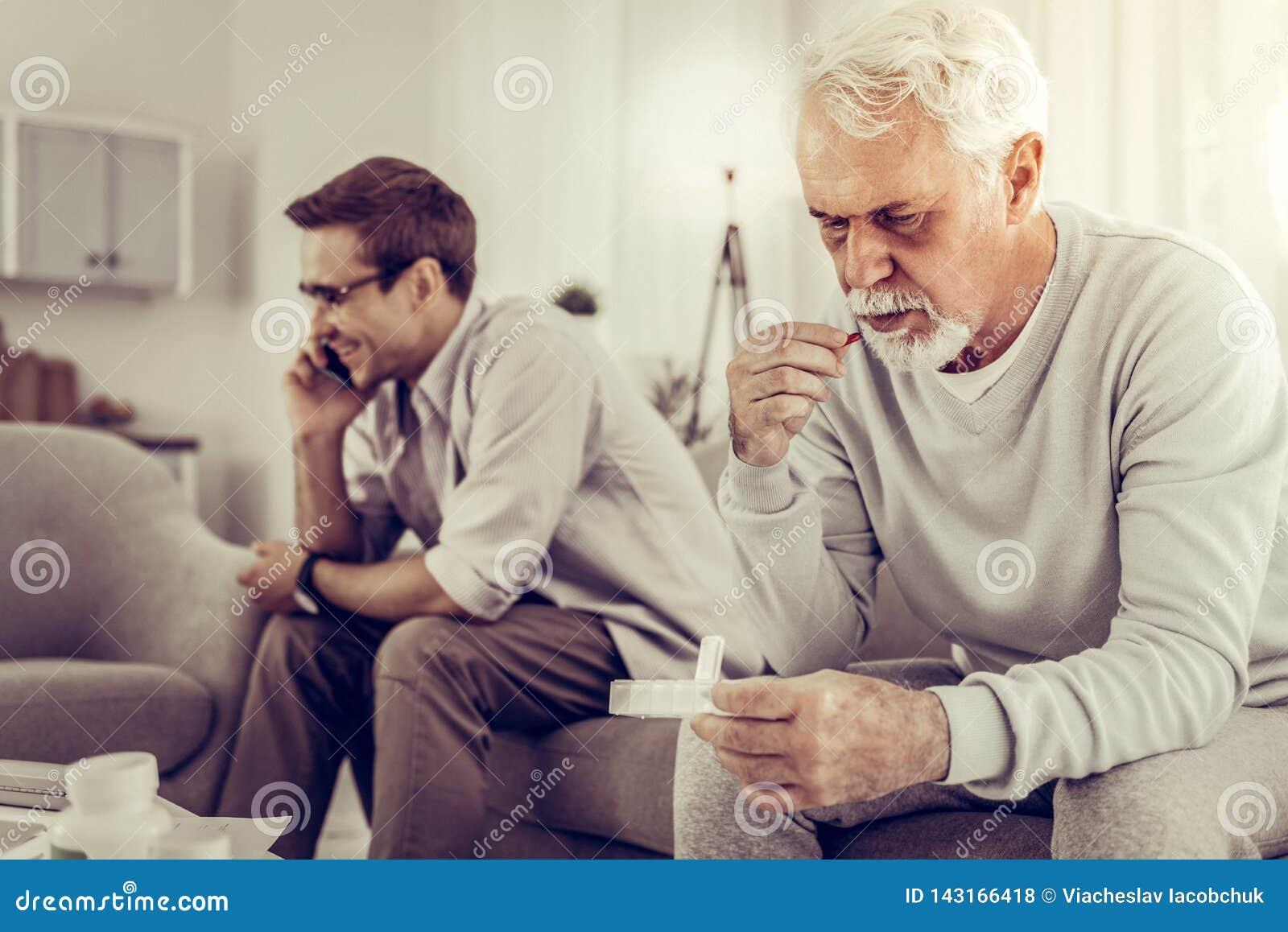 Старик принимая таблетки пока сын равнодушно имея телефонный звонок