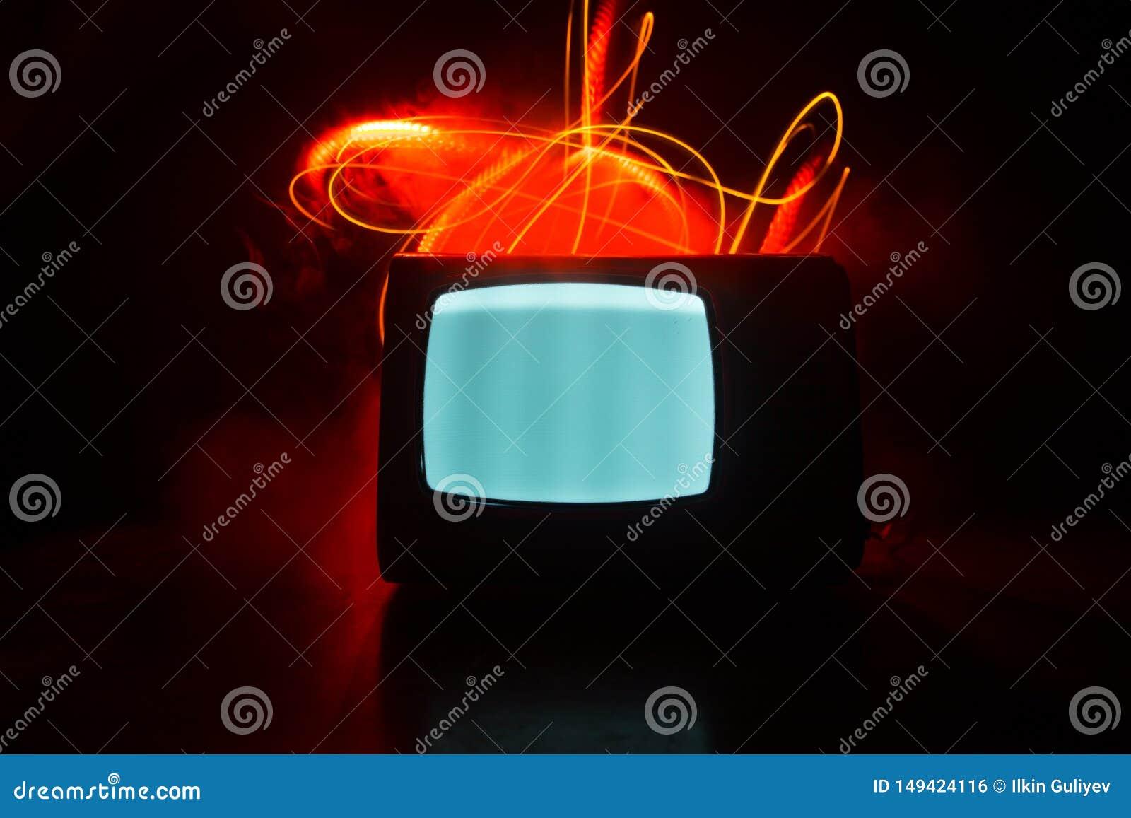Старое винтажное красное ТВ с белым шумом на темной тонизированной туманной предпосылке Ретро старый приемник телевидения отсутст