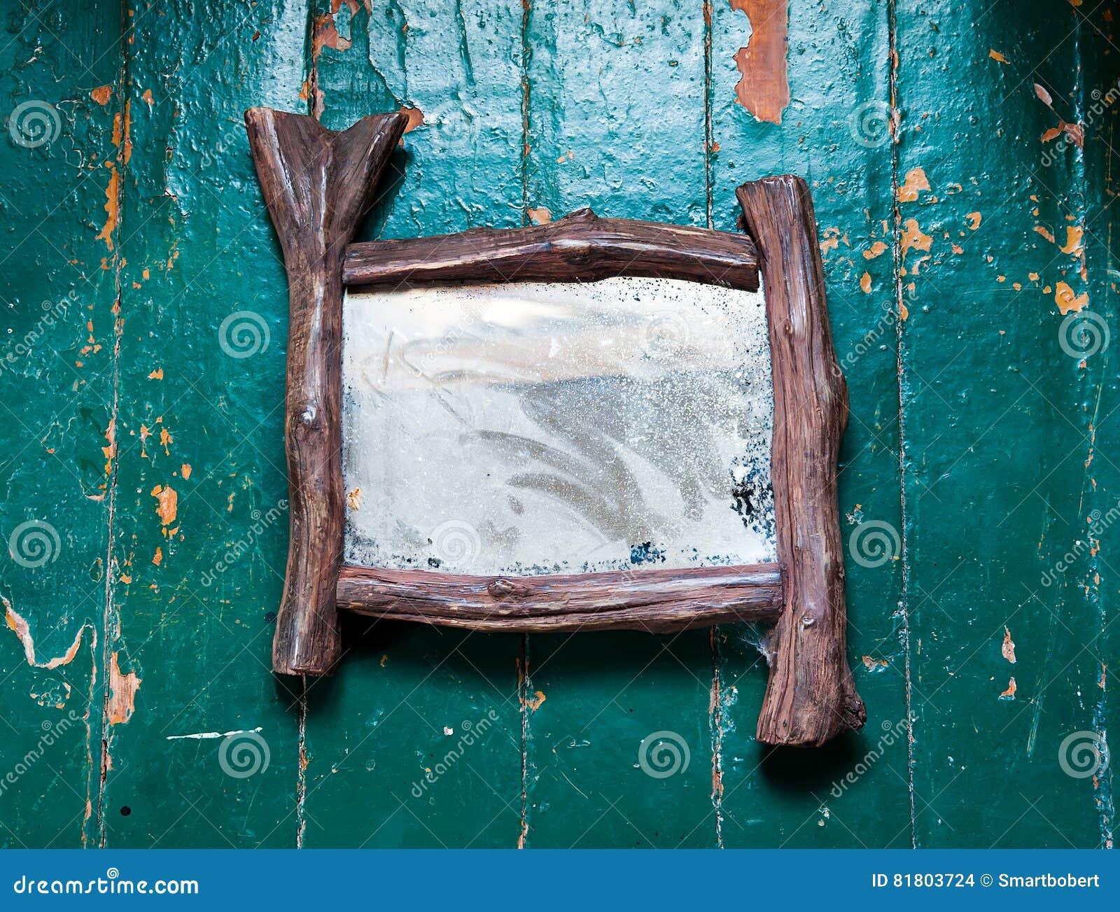 Старое пылевоздушное зеркало с паутинами и царапинами трескает на деревянным покрашенной полом краске масла