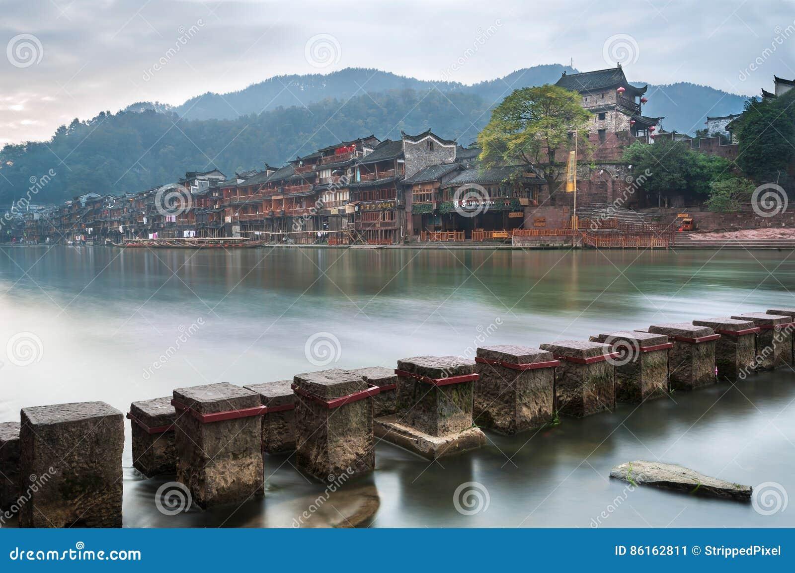 Стартовые площадки через реку Tuojiang с северным стробом возвышаются на заднем плане в Fenghuang, провинции Хунань, Китае