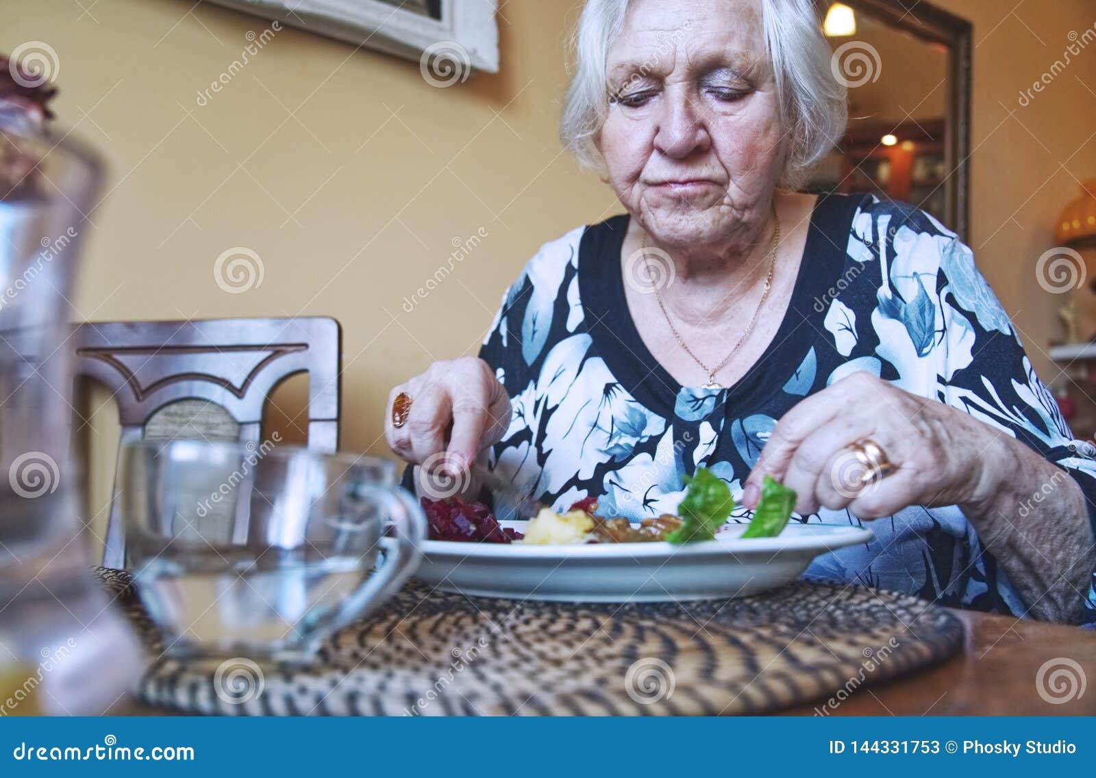 Старуха есть обедающий самостоятельно