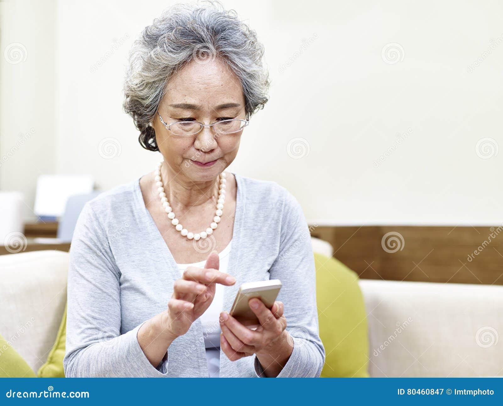 Старшая азиатская женщина используя мобильный телефон
