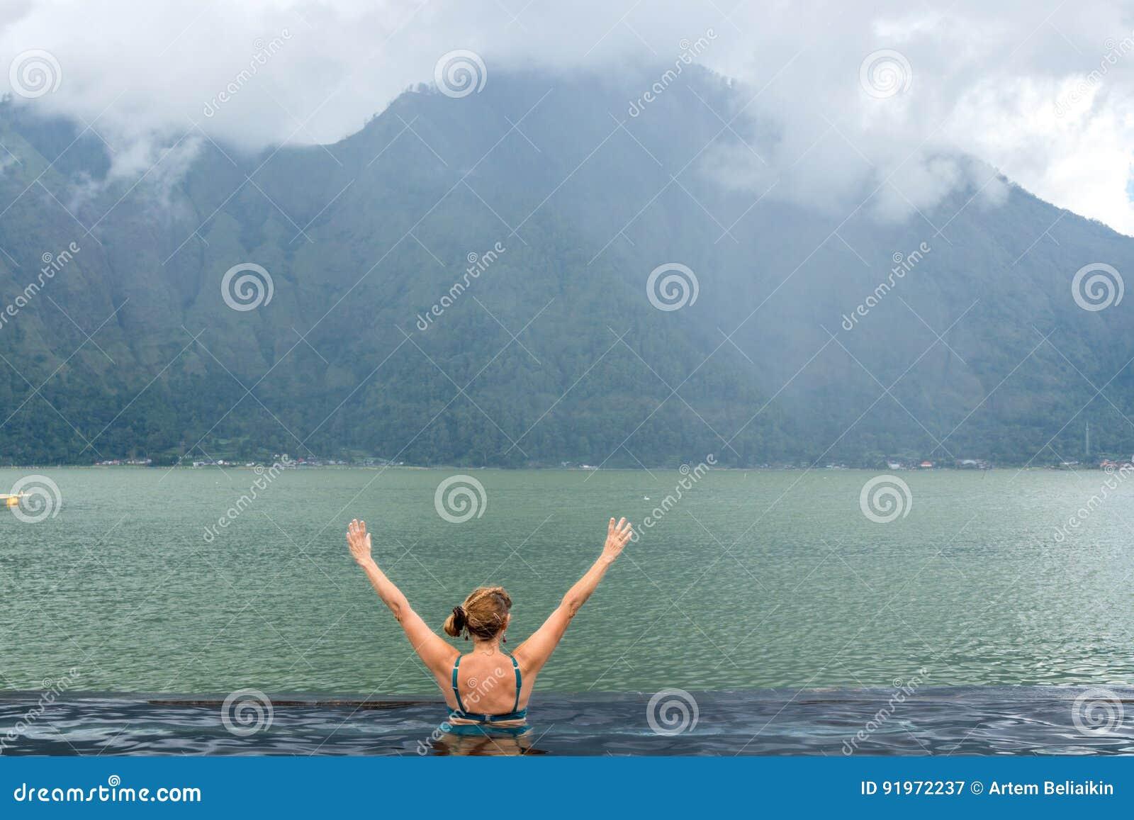 Старшая женщина в бассейне природы с изумительной предпосылкой горы Тропический остров Бали, Индонезия