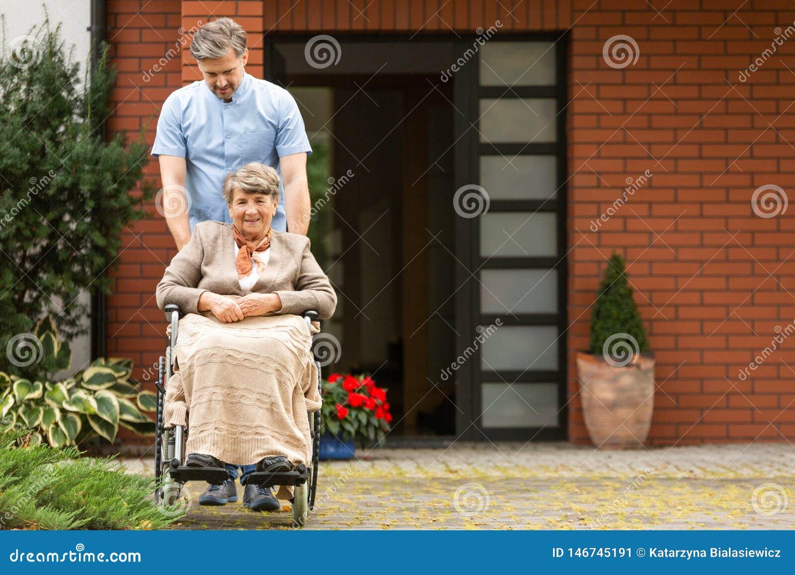 Старшая женщина в кресло-коляске поддержанной попечителем перед домом