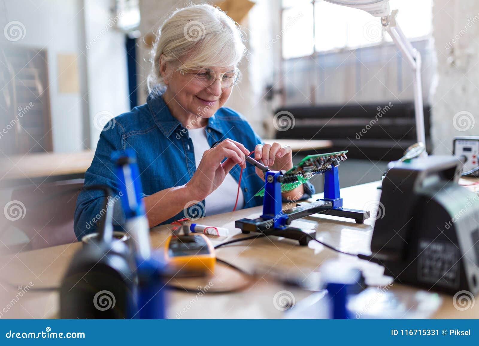 Старшая женщина в мастерской электроники