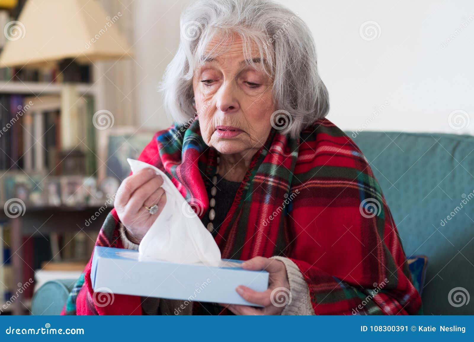 Старшая женщина дома страдая с вирусом гриппа