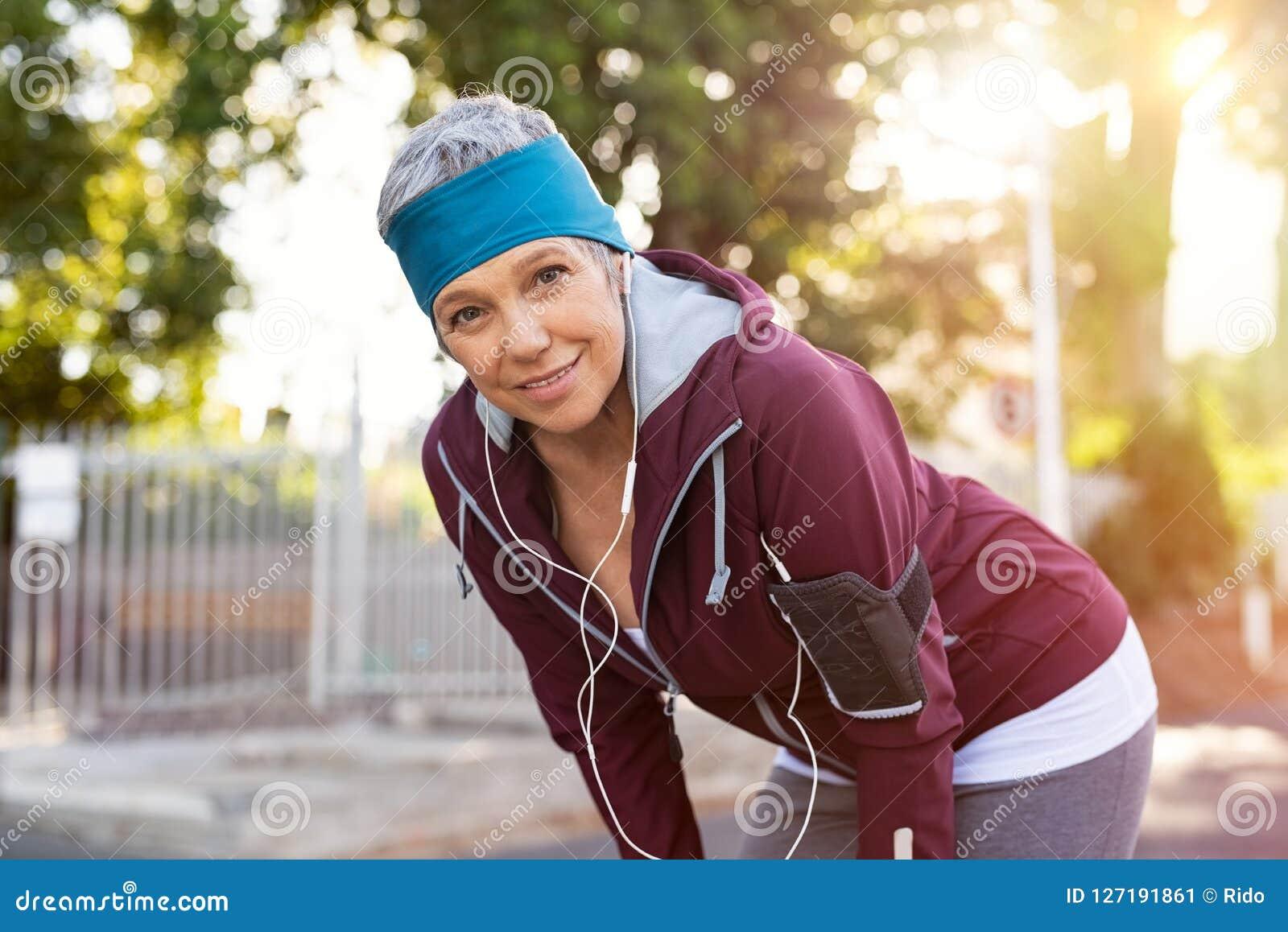Старшая женщина отдыхая после jogging