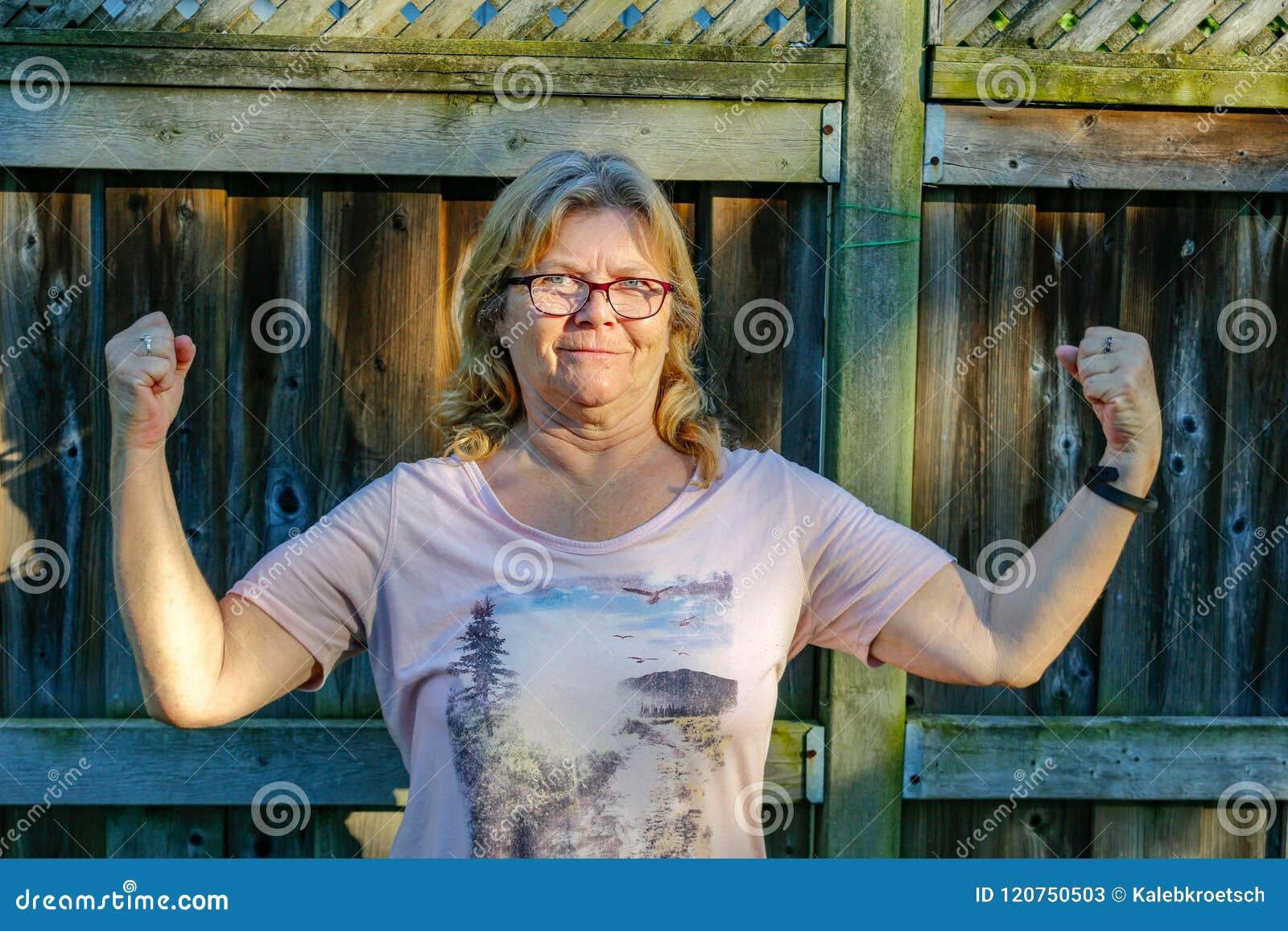 Старшая женщина принимает гордость и веселье в быть сильна и здорова