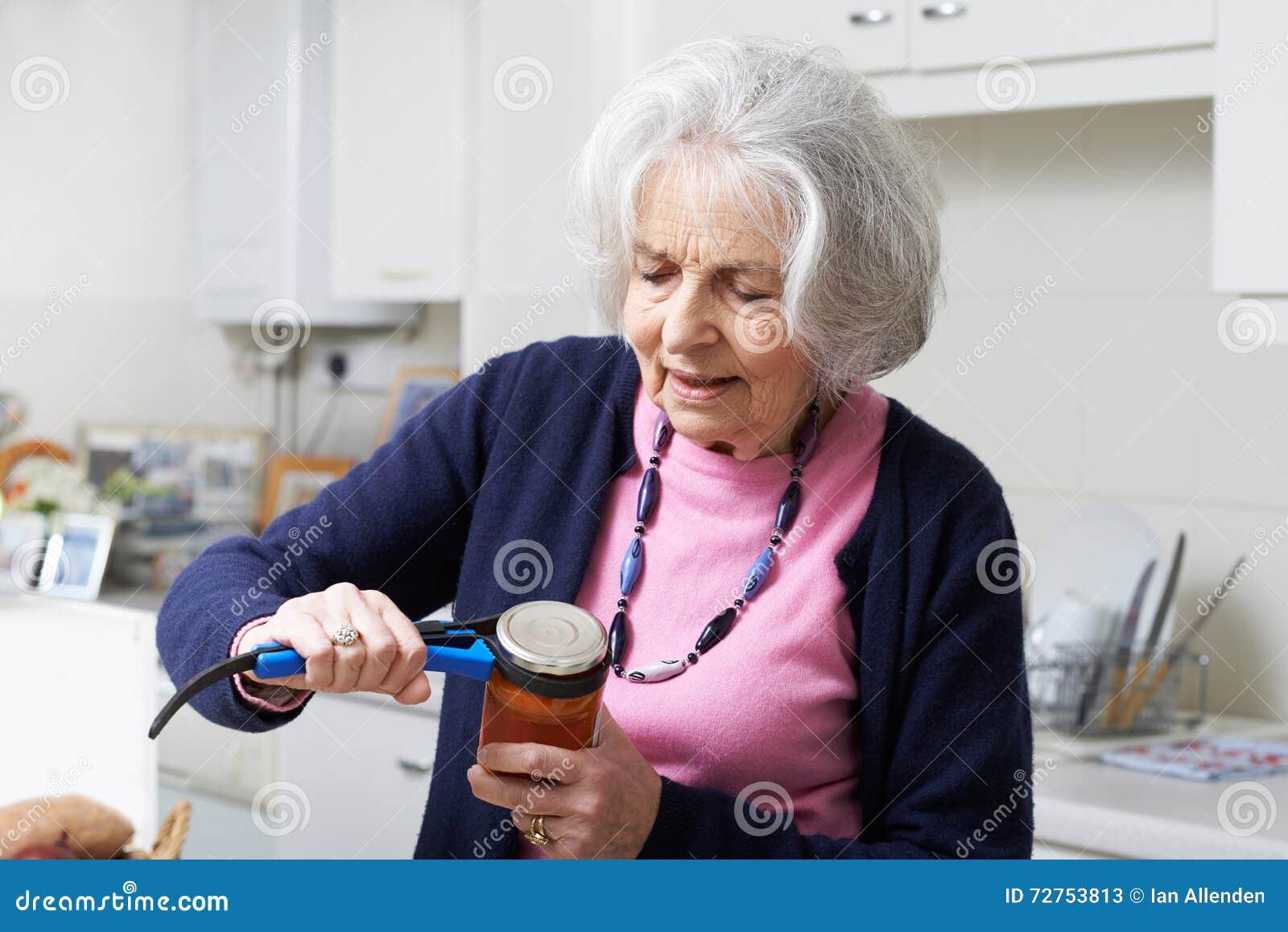 Старшая женщина принимая крышку с опарника с помощью кухни