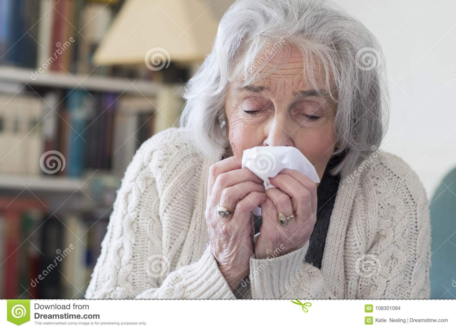 Старшая женщина с носом гриппа дуя дома