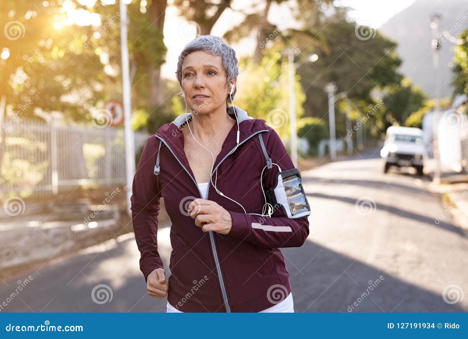 Старшая женщина jogging в улице