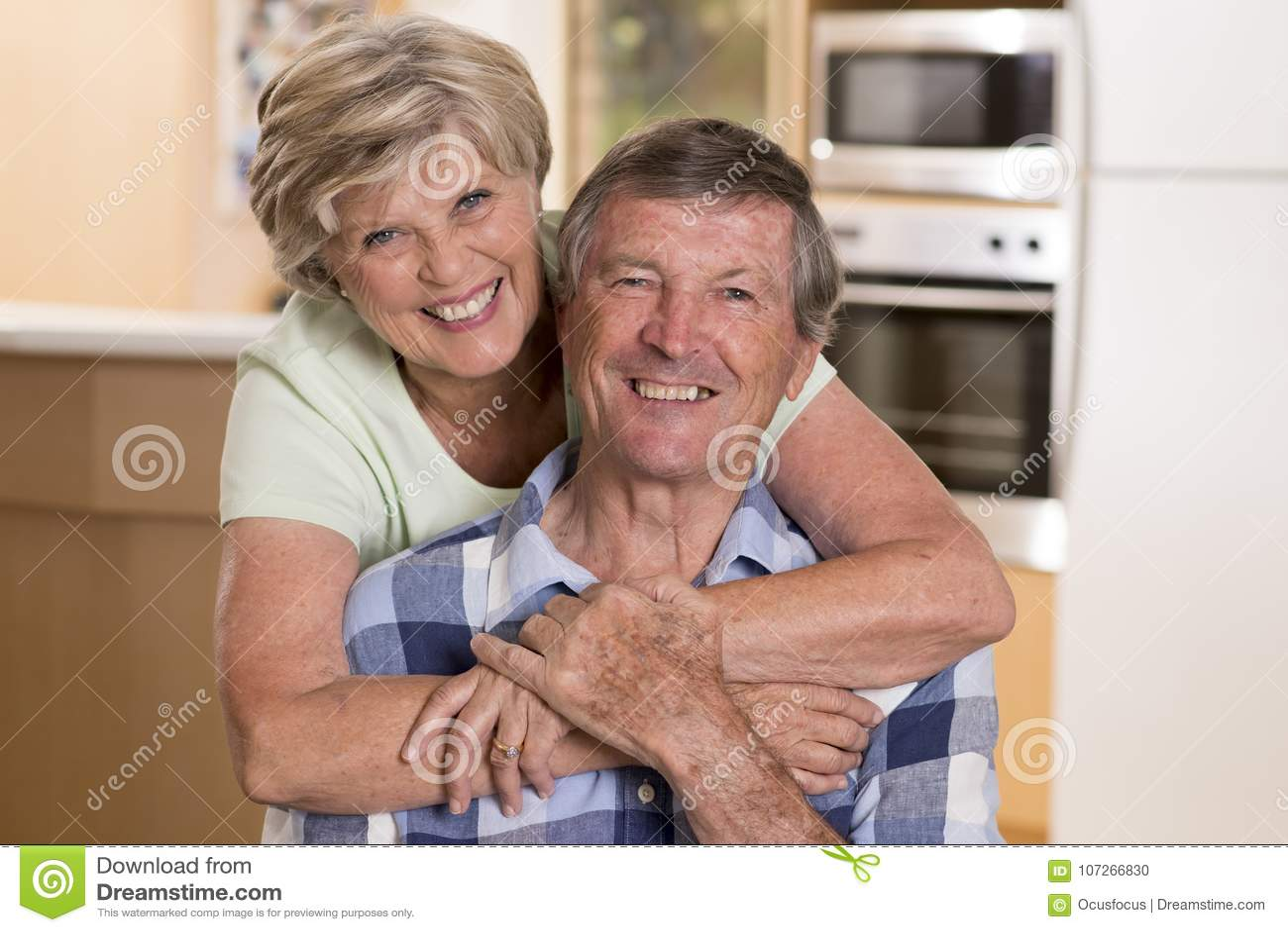 Старшая красивая кухня пар среднего возраста около 70 лет старая усмехаясь счастливая совместно дома смотря сладостный в супруге