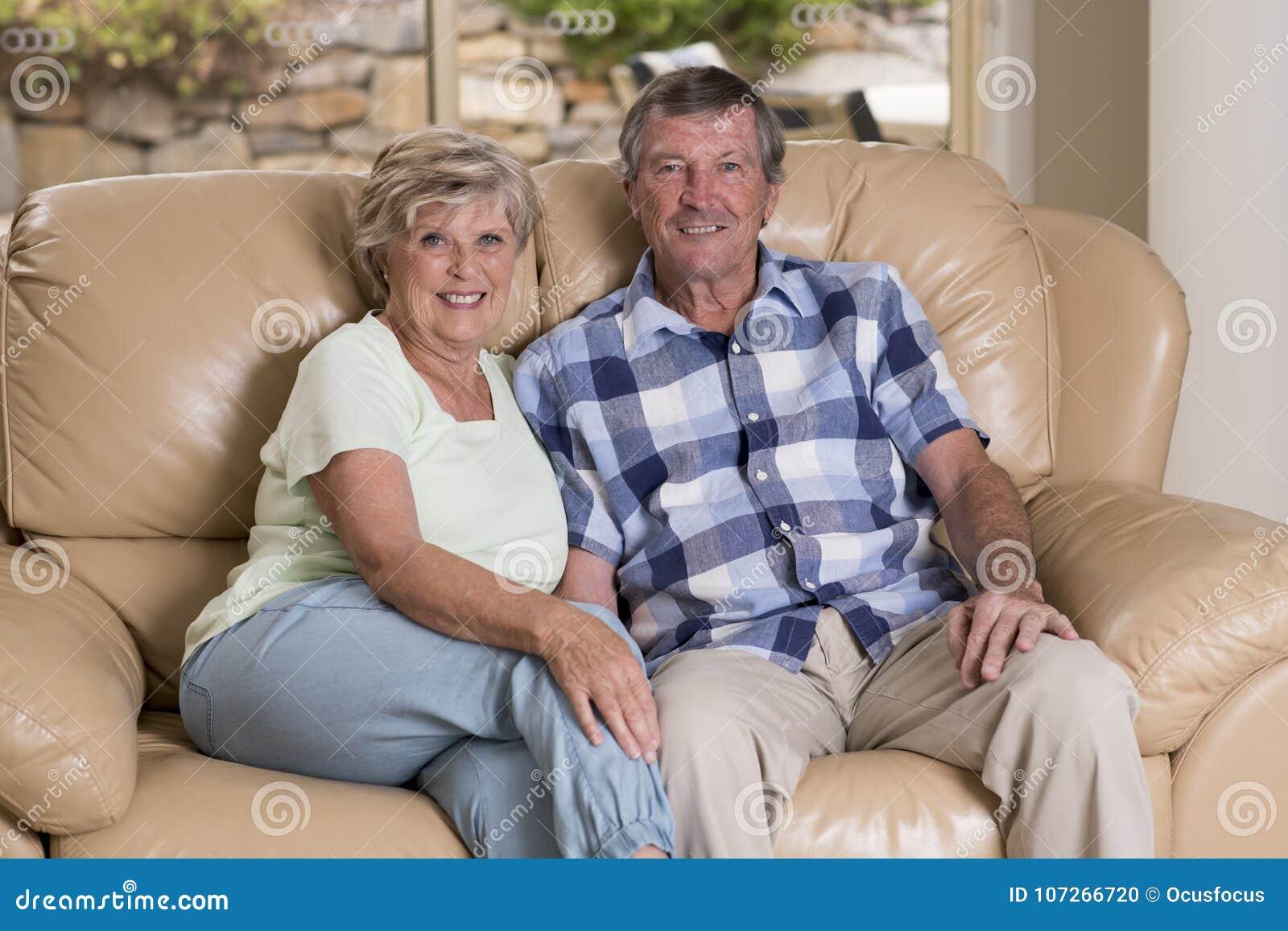 Старшее красивое кресло софы живущей комнаты пар среднего возраста около 70 лет старое усмехаясь счастливое совместно дома смотря