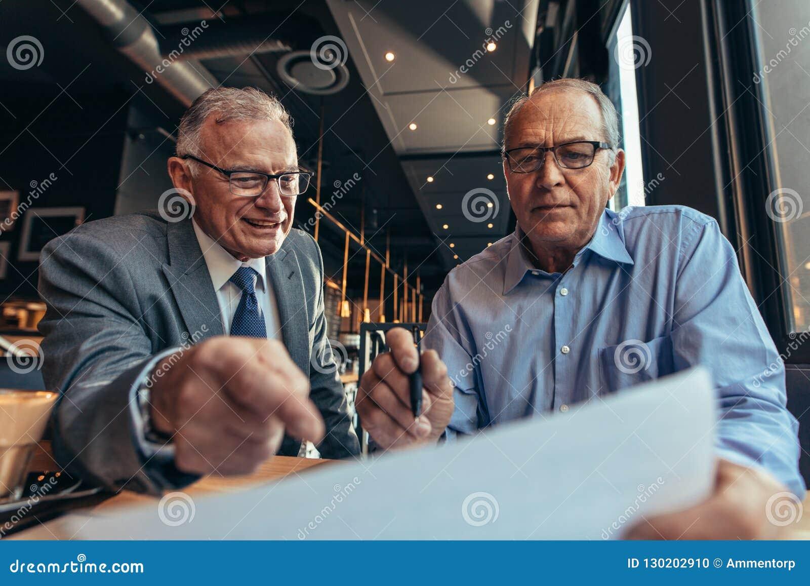 Старшие бизнесмены обсуждая на финансовом отчете