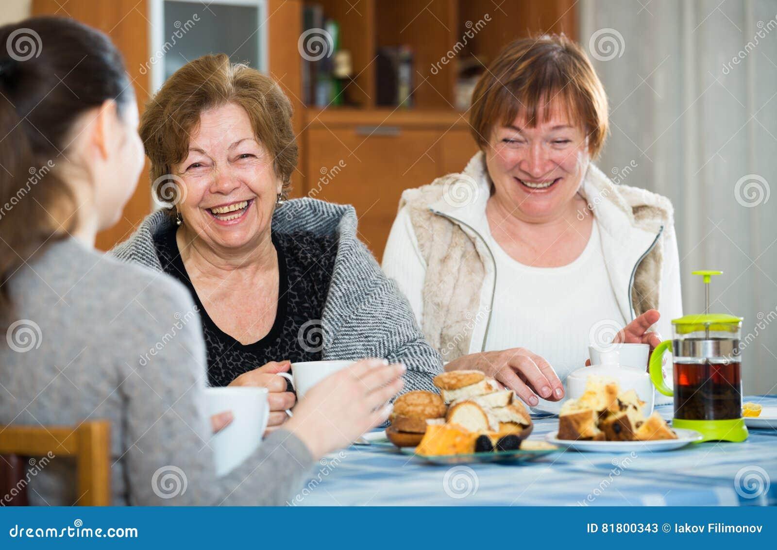 Старшие женщины разговаривая с девушкой пока выпивать чая