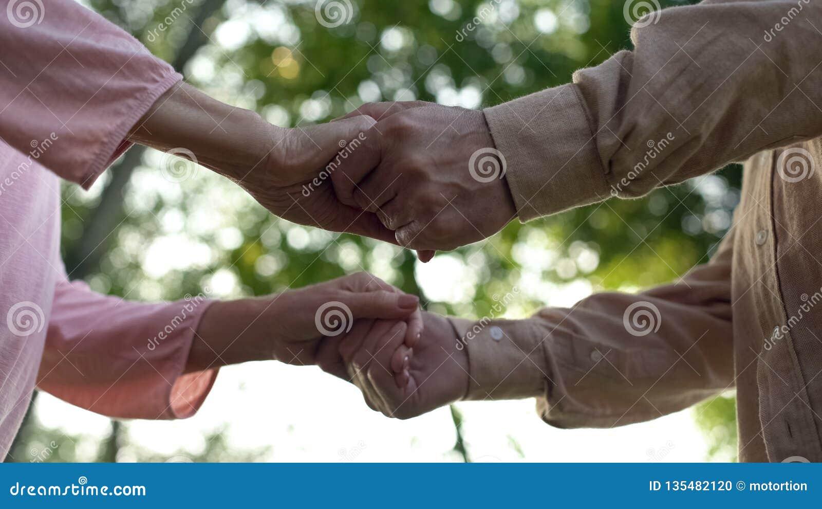 Старшие пары держа руки, встречая старость совместно, близкие отношения, забота
