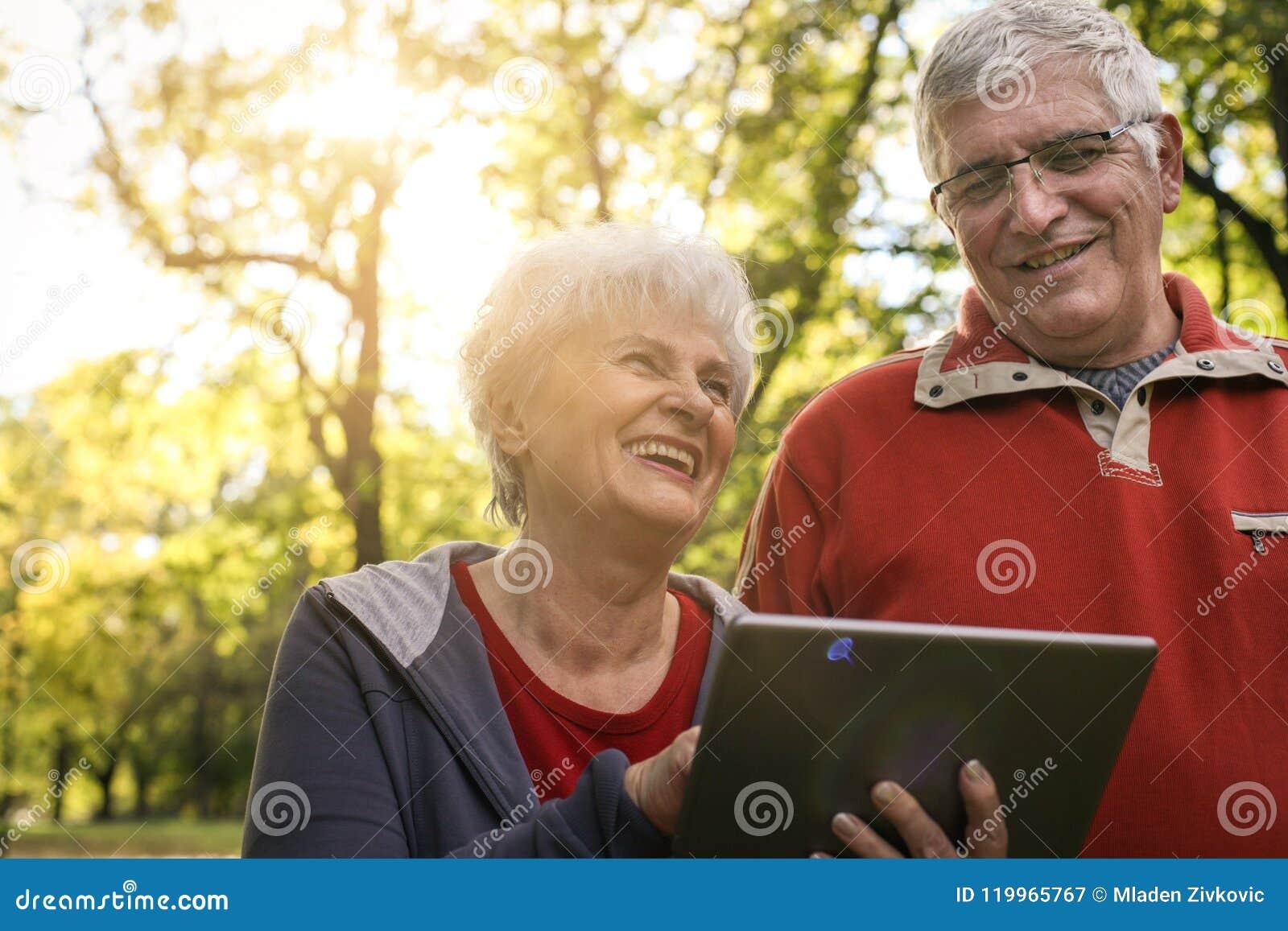 Старшие пары наслаждаясь в парке совместно и используя число