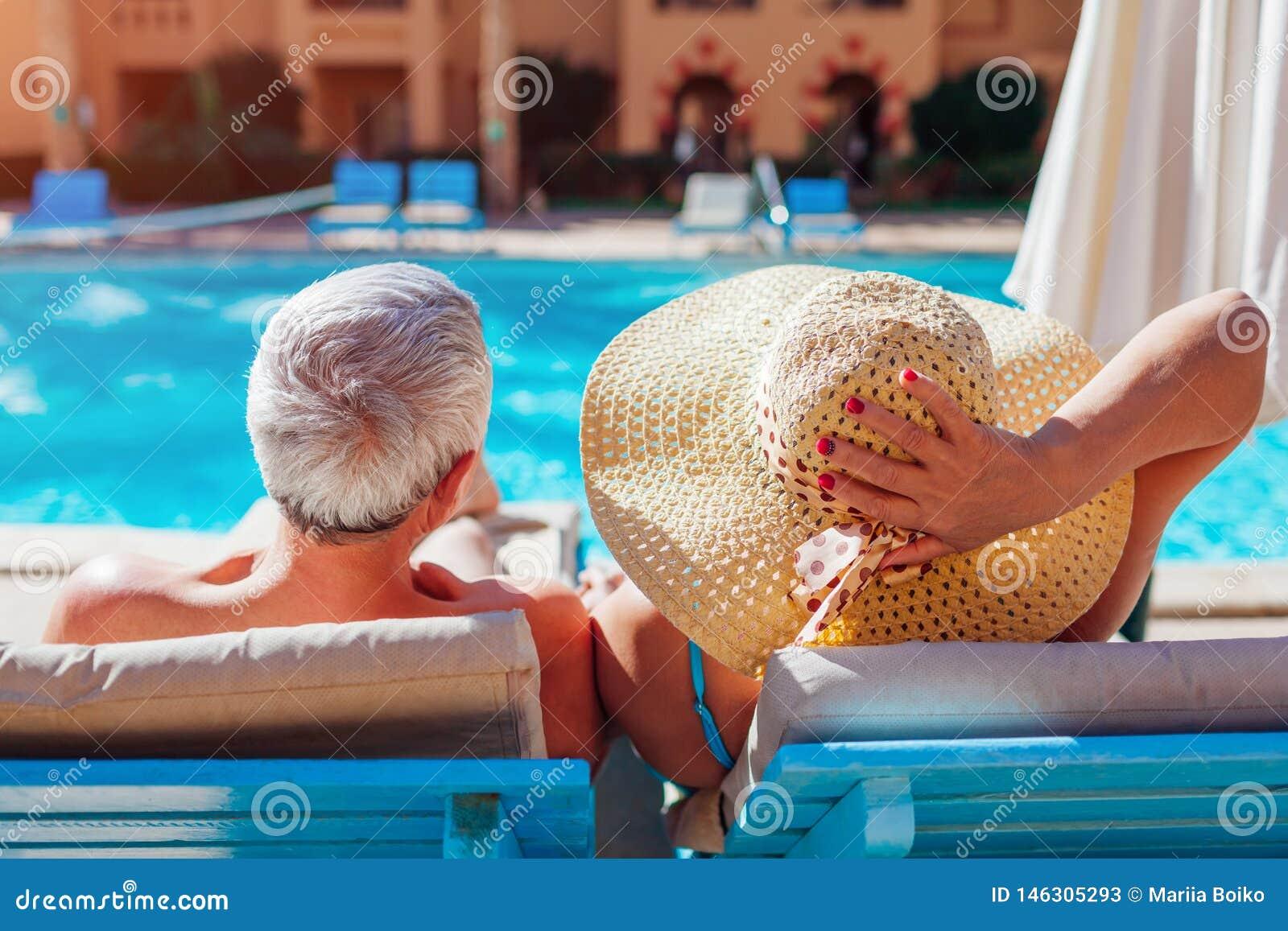 Старшие пары ослабляя бассейном лежа на шезлонгах Люди наслаждаясь летними каникулами