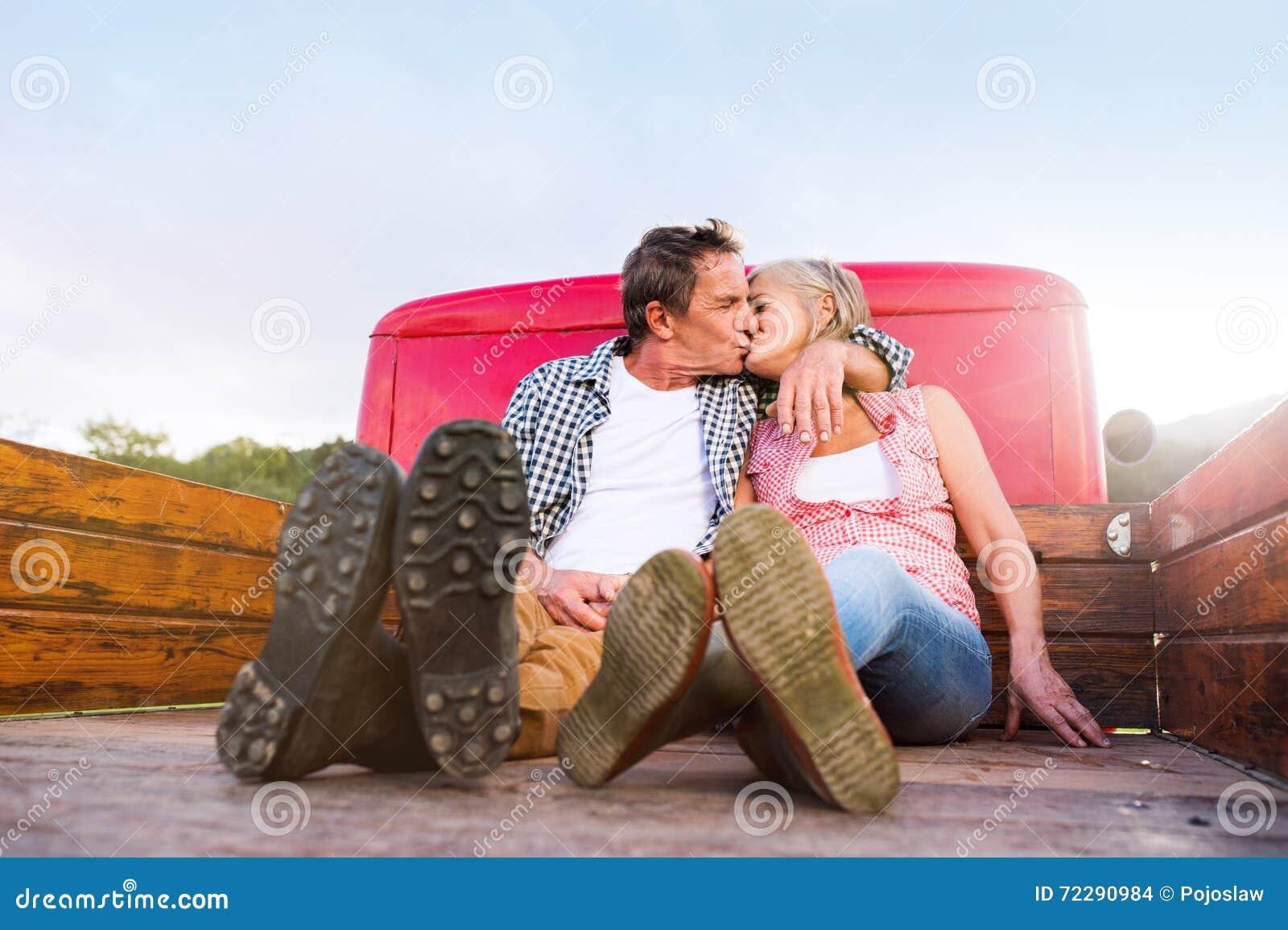 Download Старшие пары сидя внутри подпирают красного грузового пикапа Стоковое Фото - изображение насчитывающей green, падение: 72290984