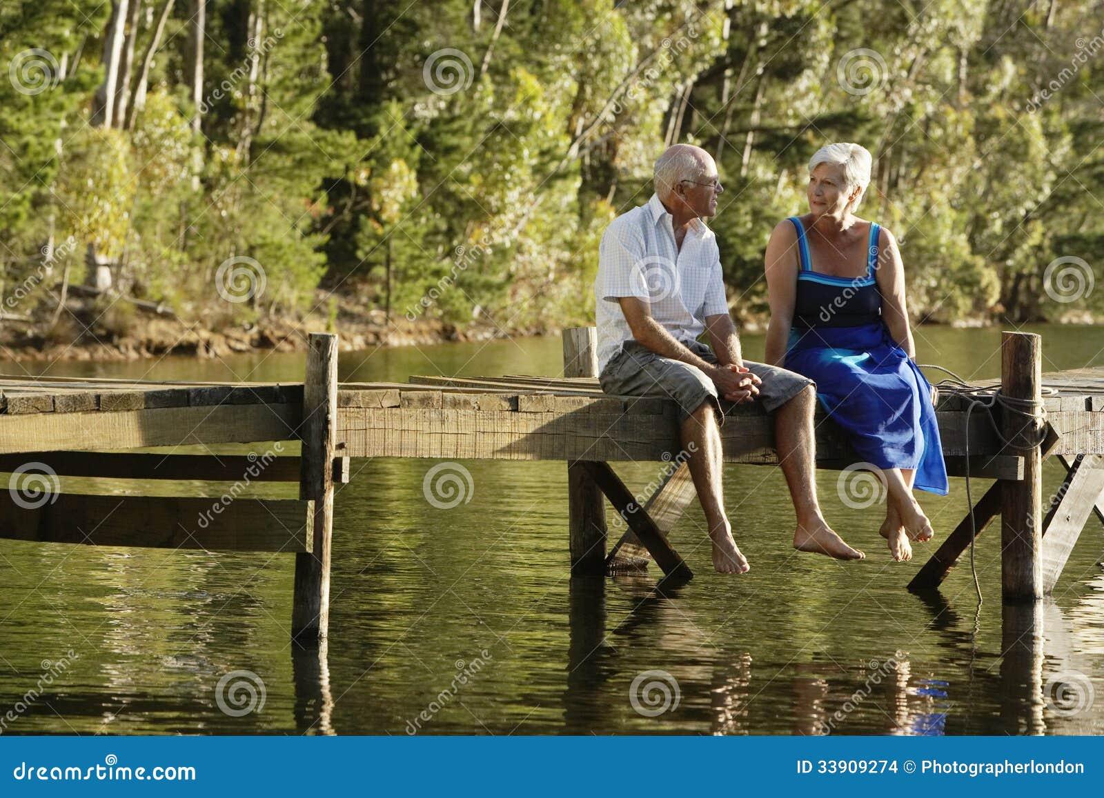 Старшие пары сидя на пристани на озере