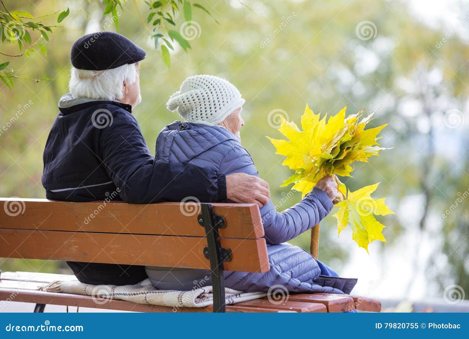Старшие пары сидя на стенде в парке