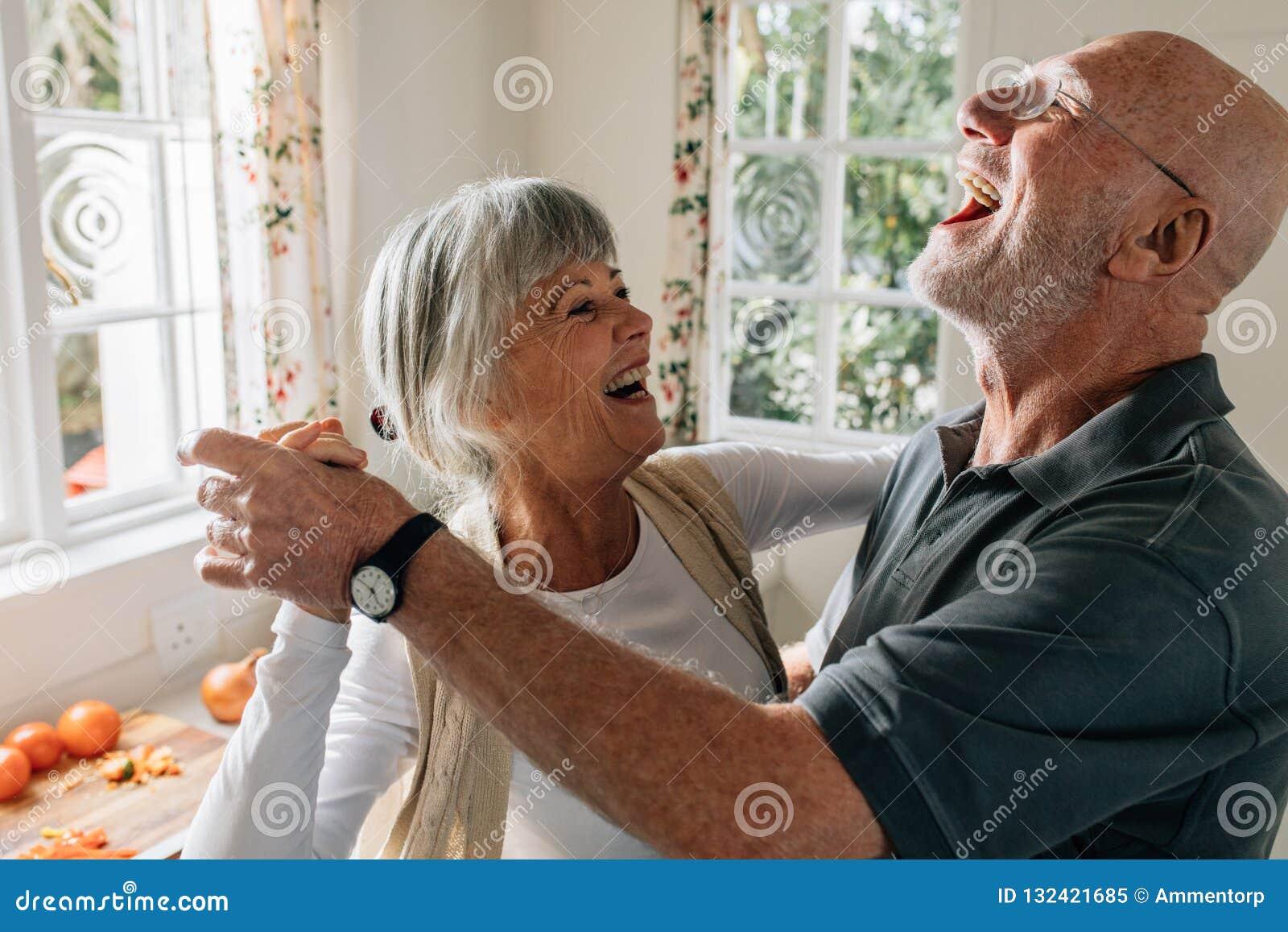 Старшие пары смеясь и имея танцевать потехи