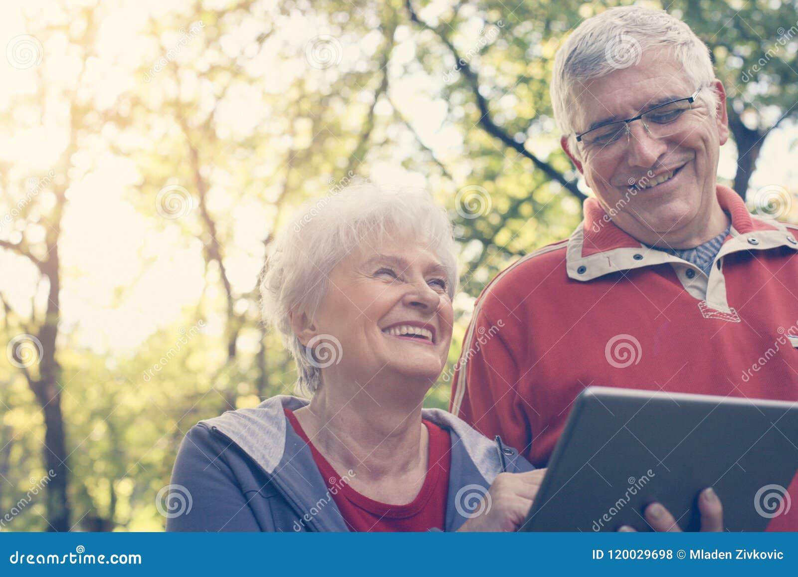 Старшие пары стоя в парке и используя iPod конец вверх
