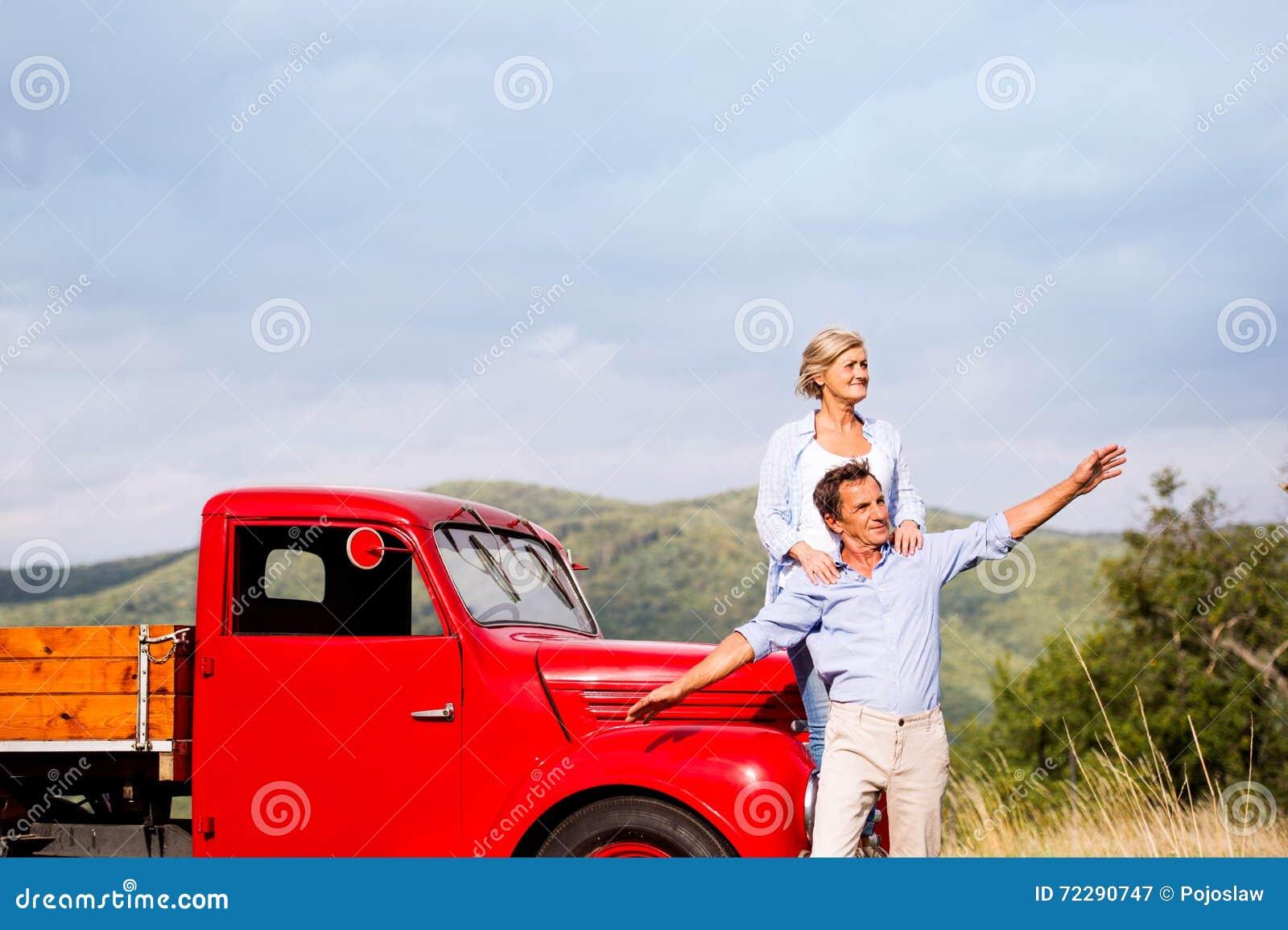 Download Старшие пары стоя на красном винтажном автомобиле Стоковое Изображение - изображение насчитывающей лето, automobiled: 72290747