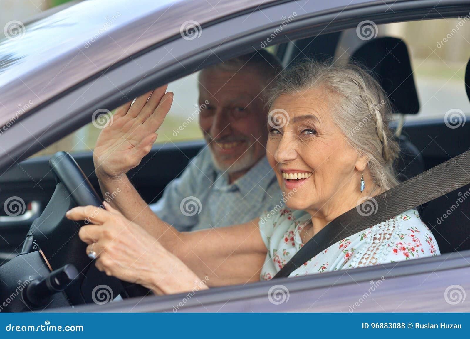 Старшие пары управляя автомобилем