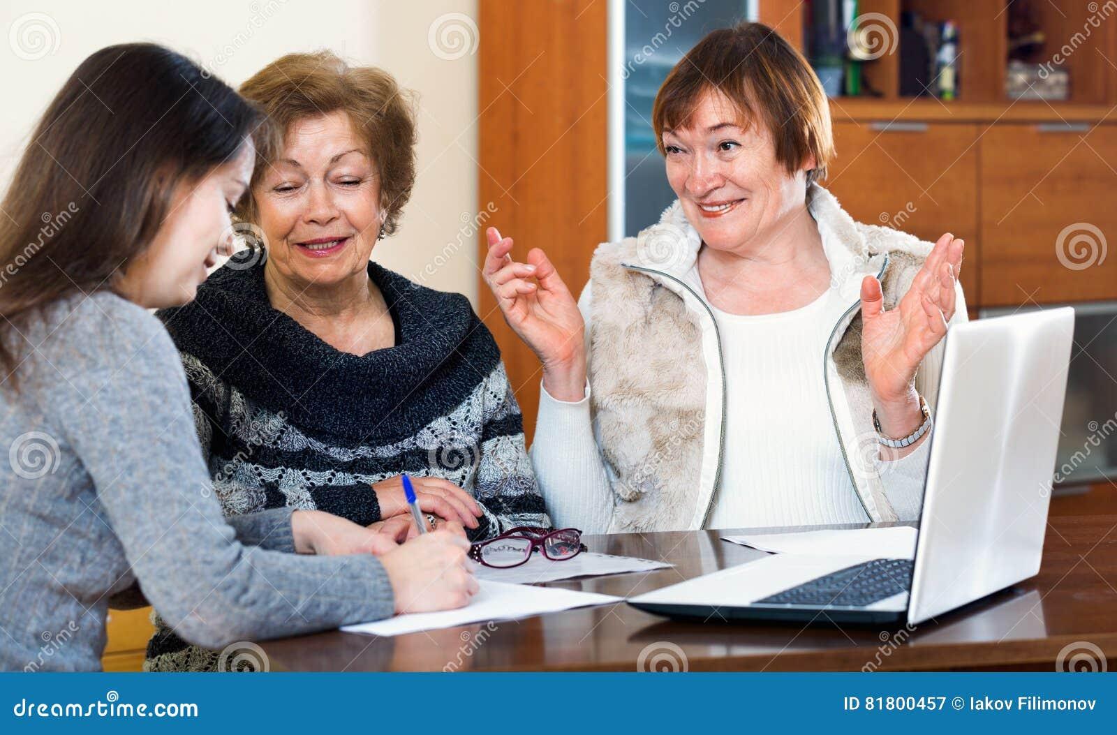 Старшие радостные женщины делая будут на общественной нотариальной конторе