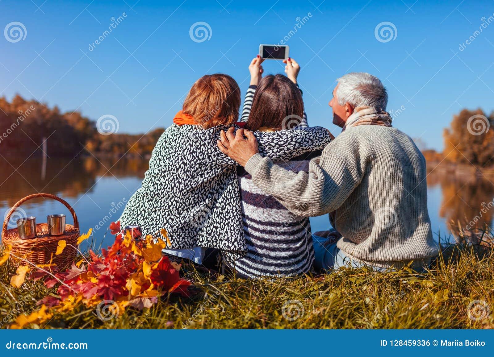 Старшие родители принимая selfie озером осени с их взрослой дочерью Семейные ценности иметь пикник людей