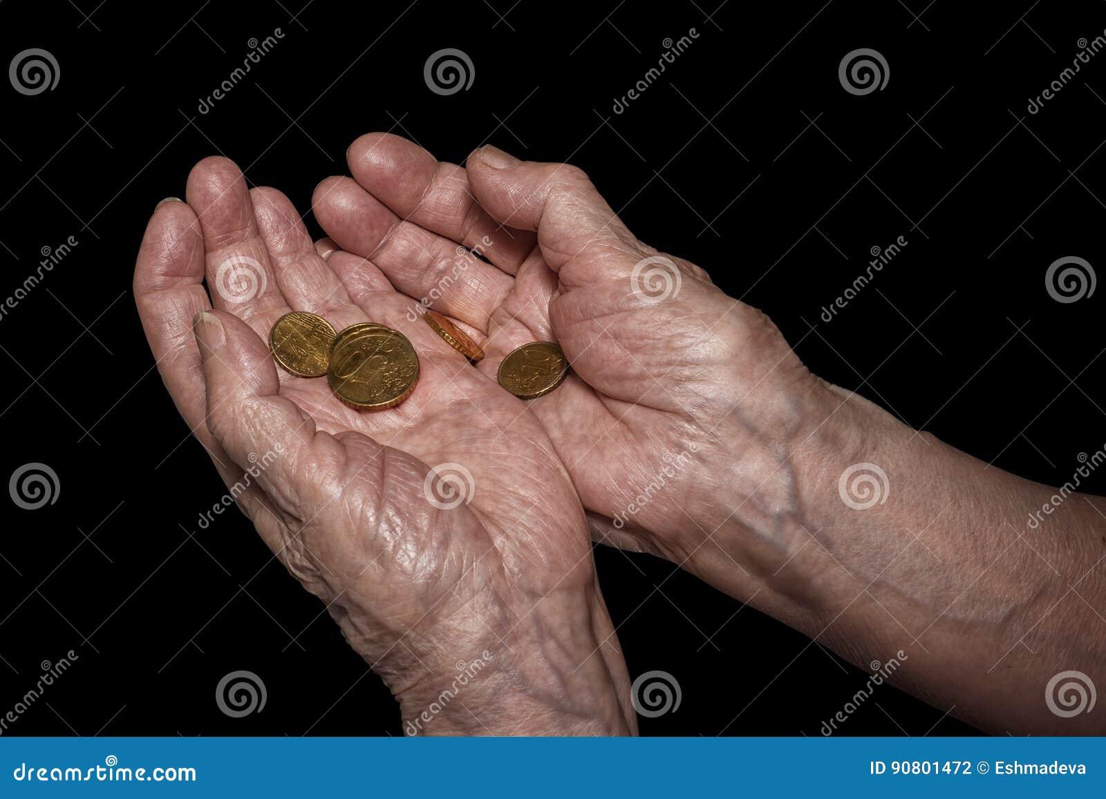 Старшие руки женщины держа некоторые монетки евро Пенсия, бедность, так