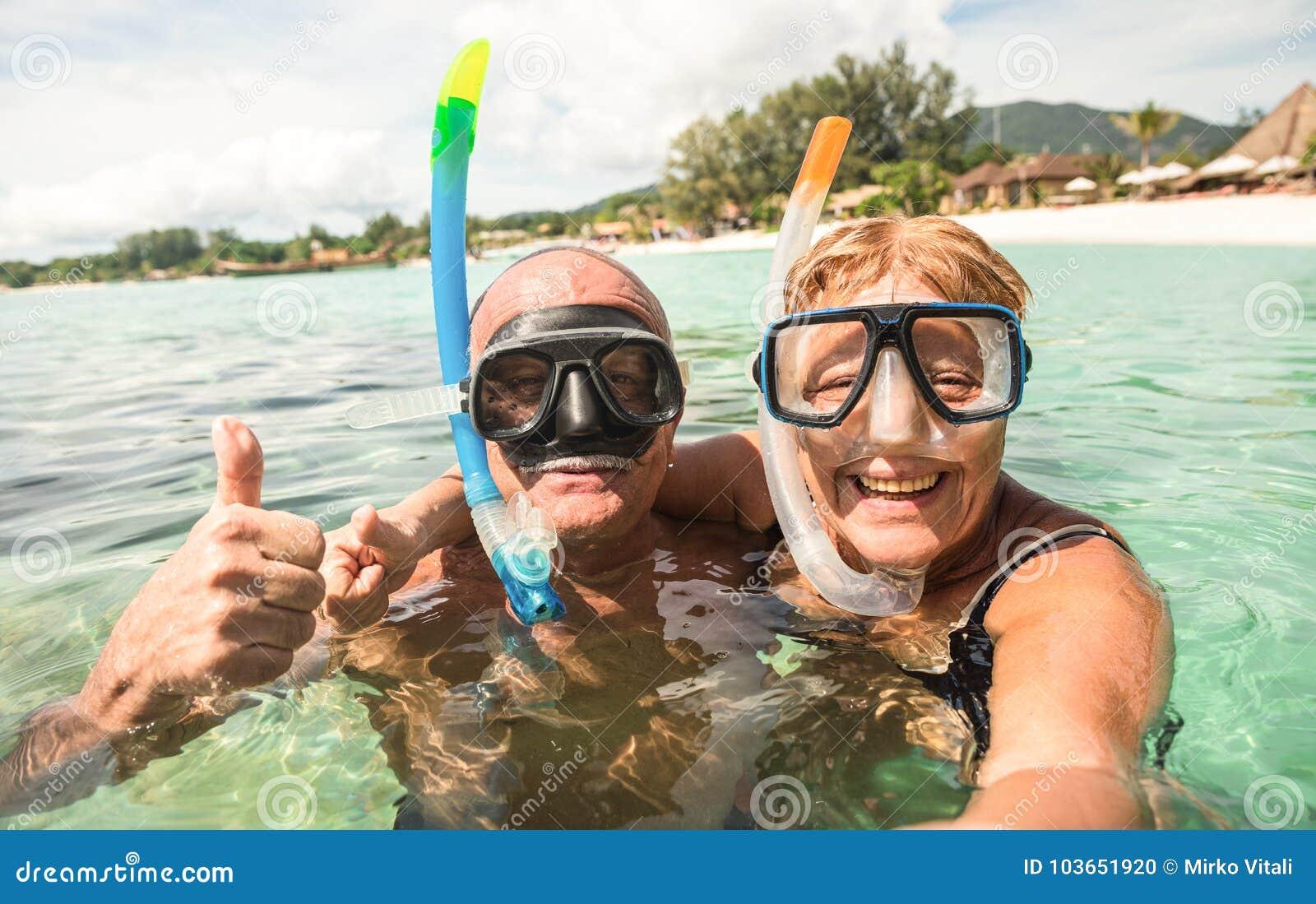 Старшие счастливые пары принимая selfie с масками акваланга snorkeling