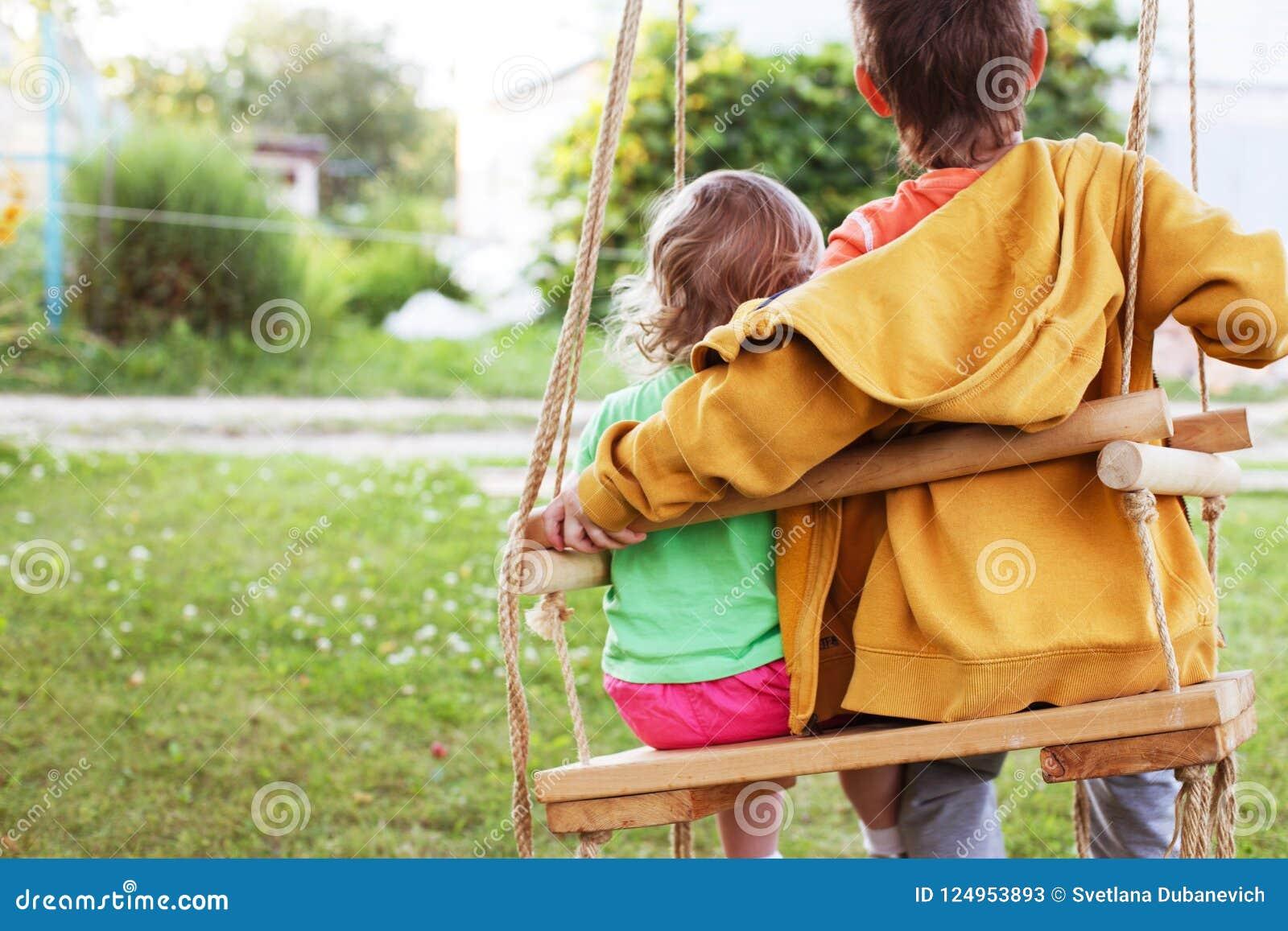 Старший брат обнимая маленькую сестру