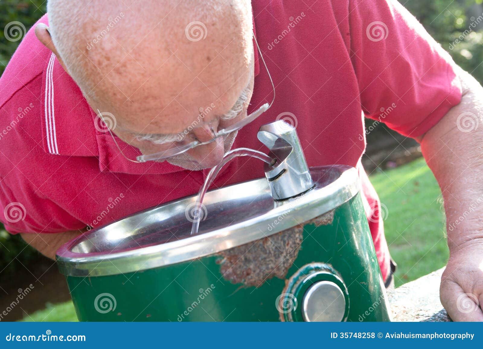Старший выпивать от фонтана