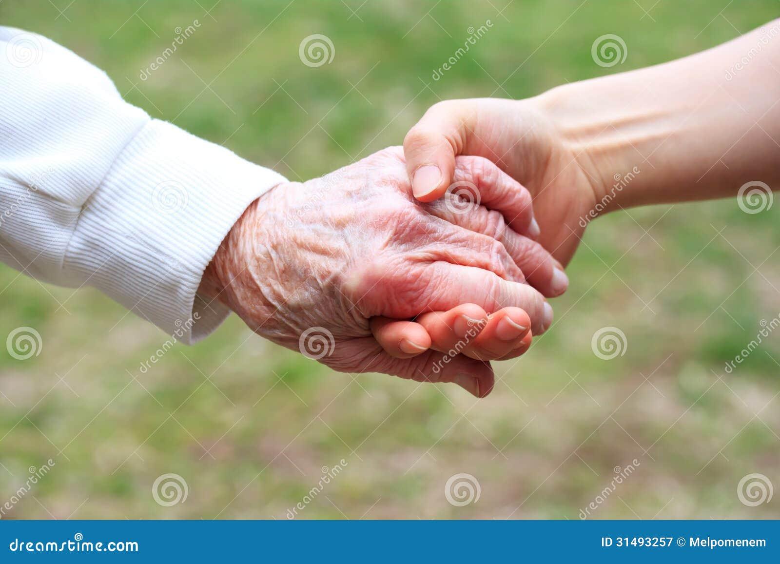 Старший и молодые женщины держа руки