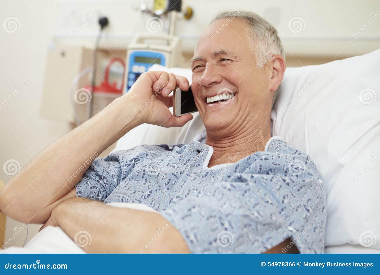 Старший мужской пациент используя мобильный телефон в больничной койке