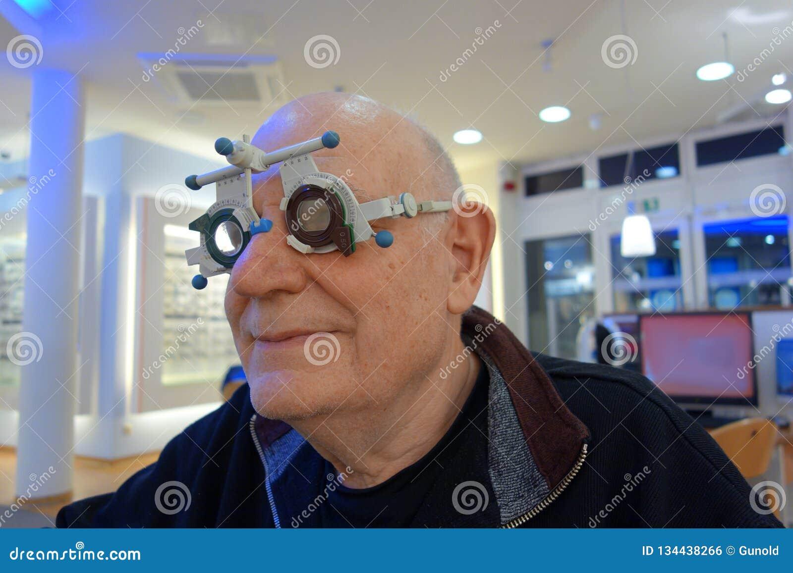 Старший на optician испытывая новые объективы в рамке следа