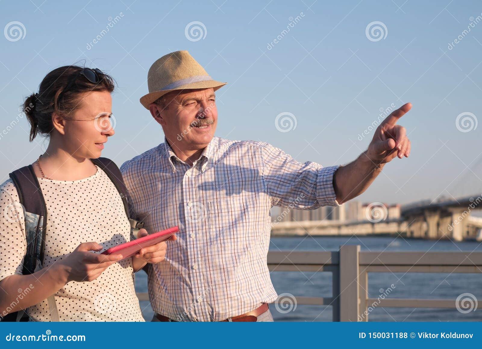 Старший человек в шляпе лета показывает путь на карте к молодой женщине