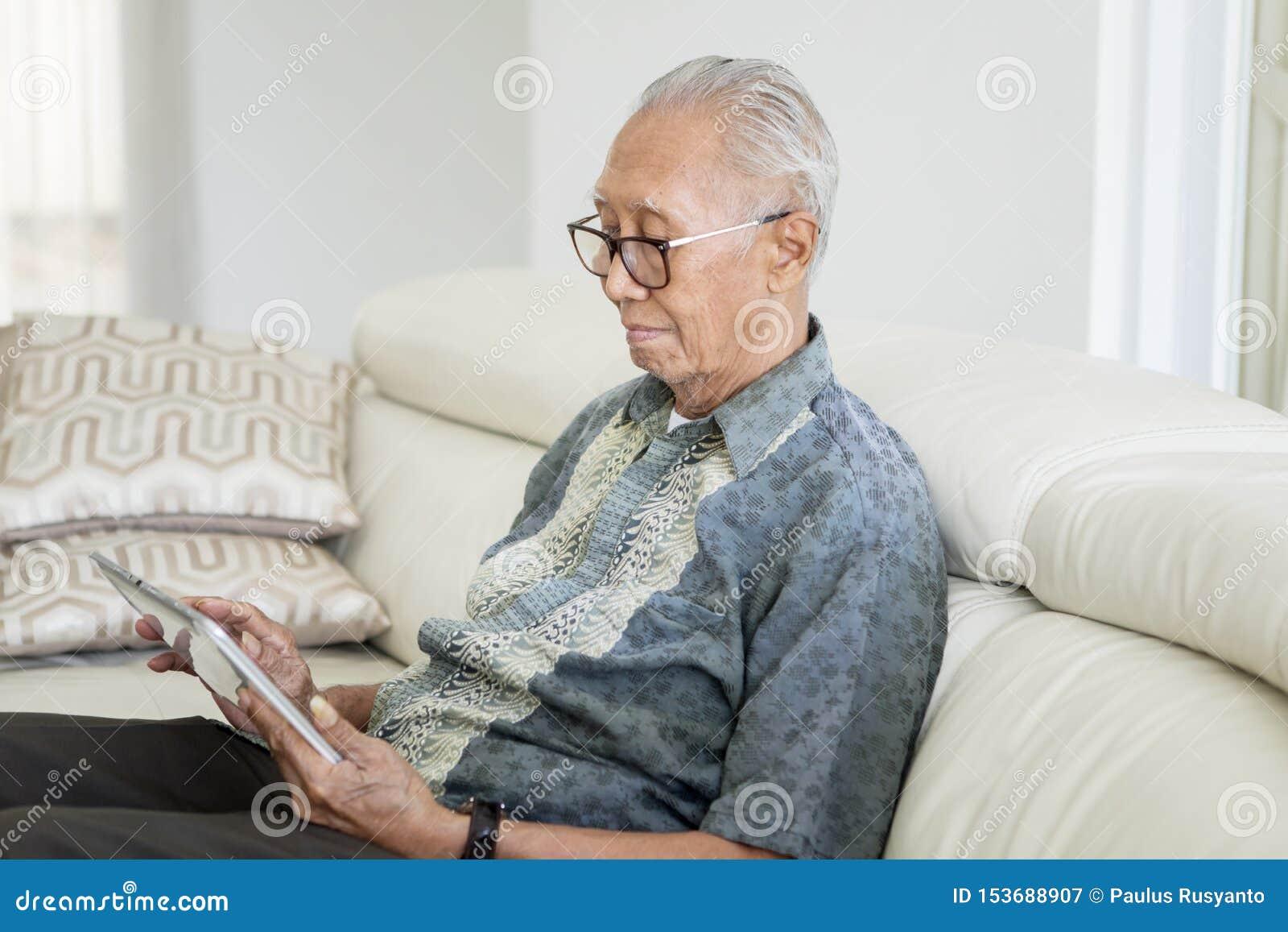 Старший человек используя цифровой планшет