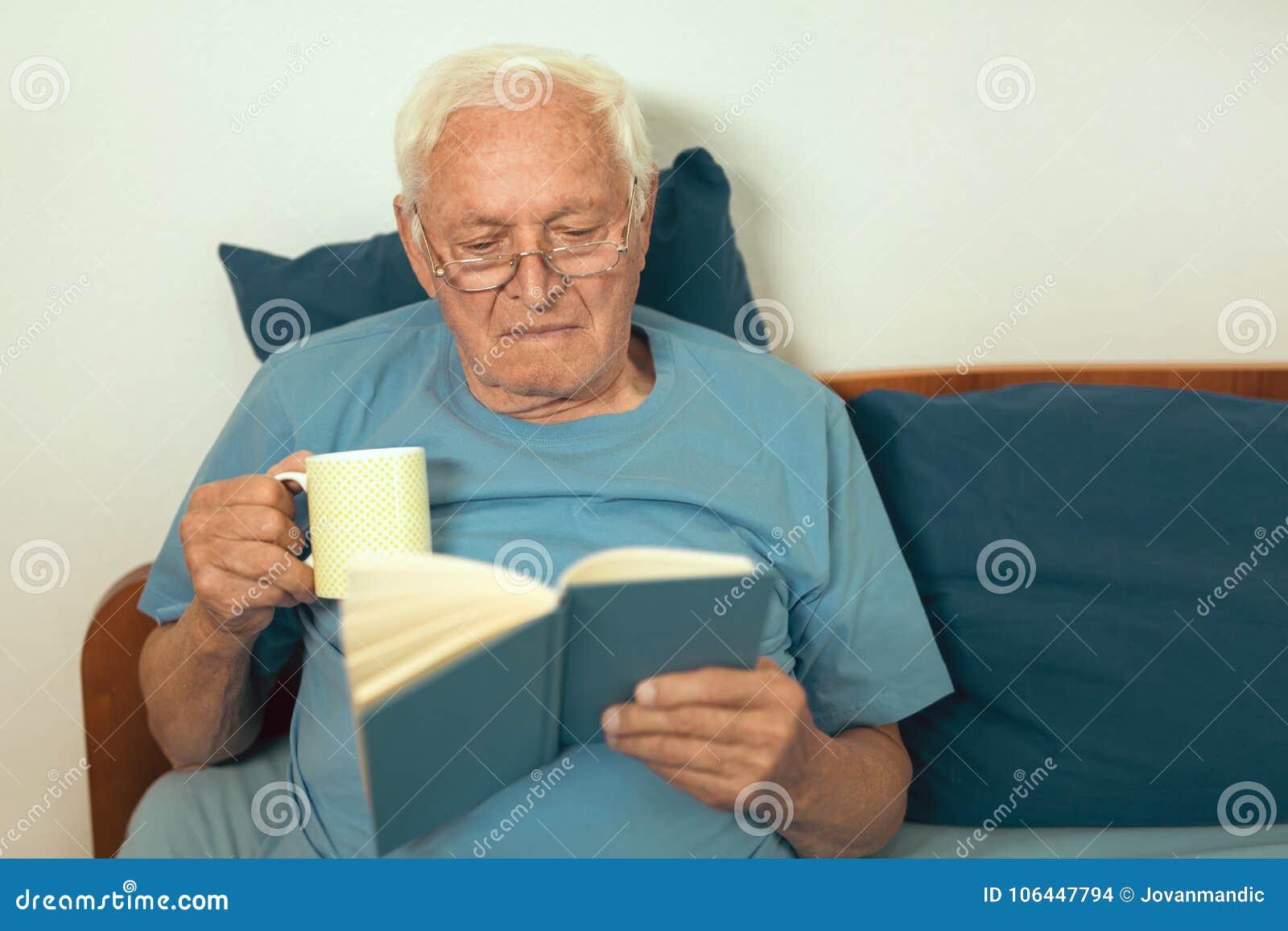 Старший человек лежа на книге неудачи и чтения
