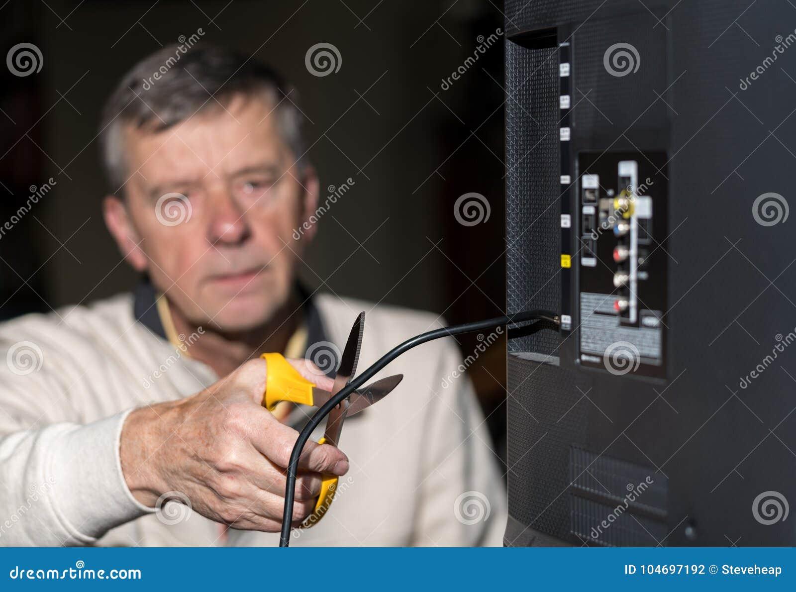 Старший человек режа шнур на его пакете кабельного телевидения