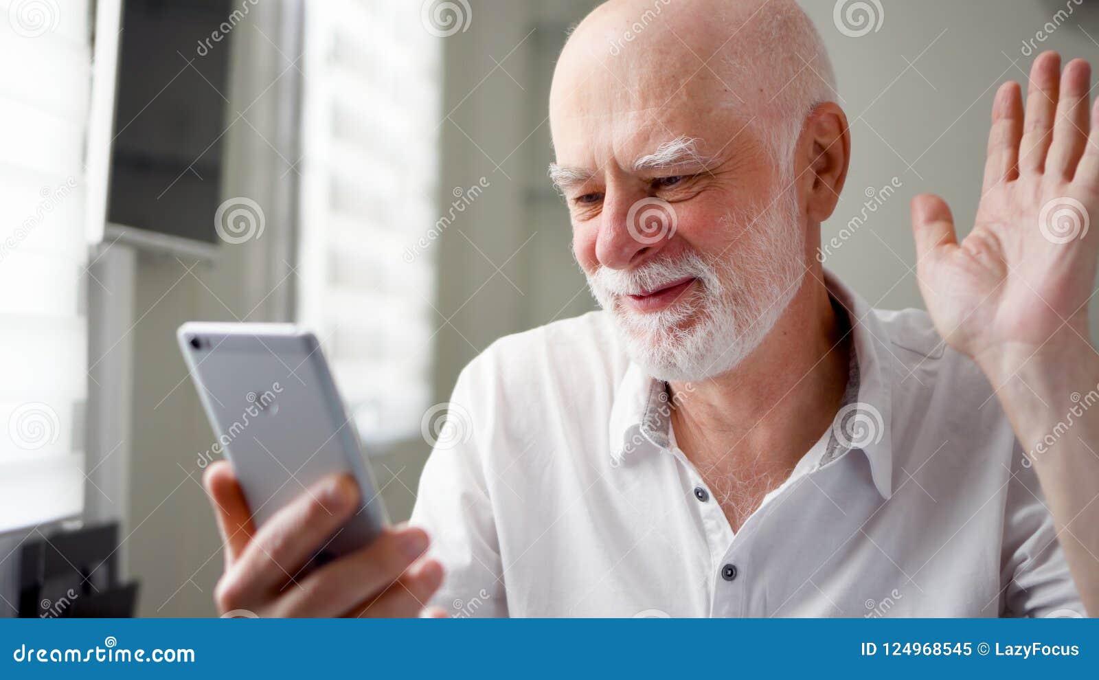 Старший человек сидя дома с smartphone Используя передвижной говорить через посыльный app Усмехаясь развевая рука в приветствии