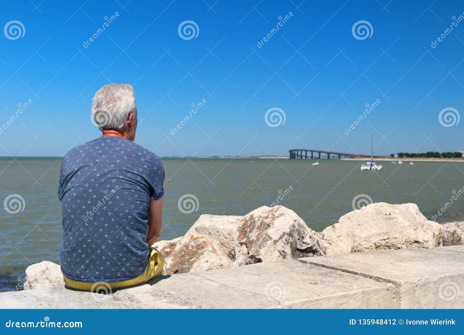 Старший человек сидя на побережье