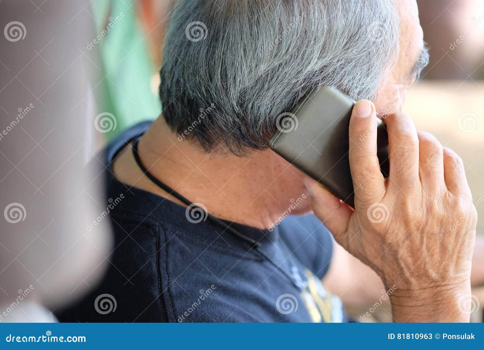 Старший человек наслаждаясь на его телефоне