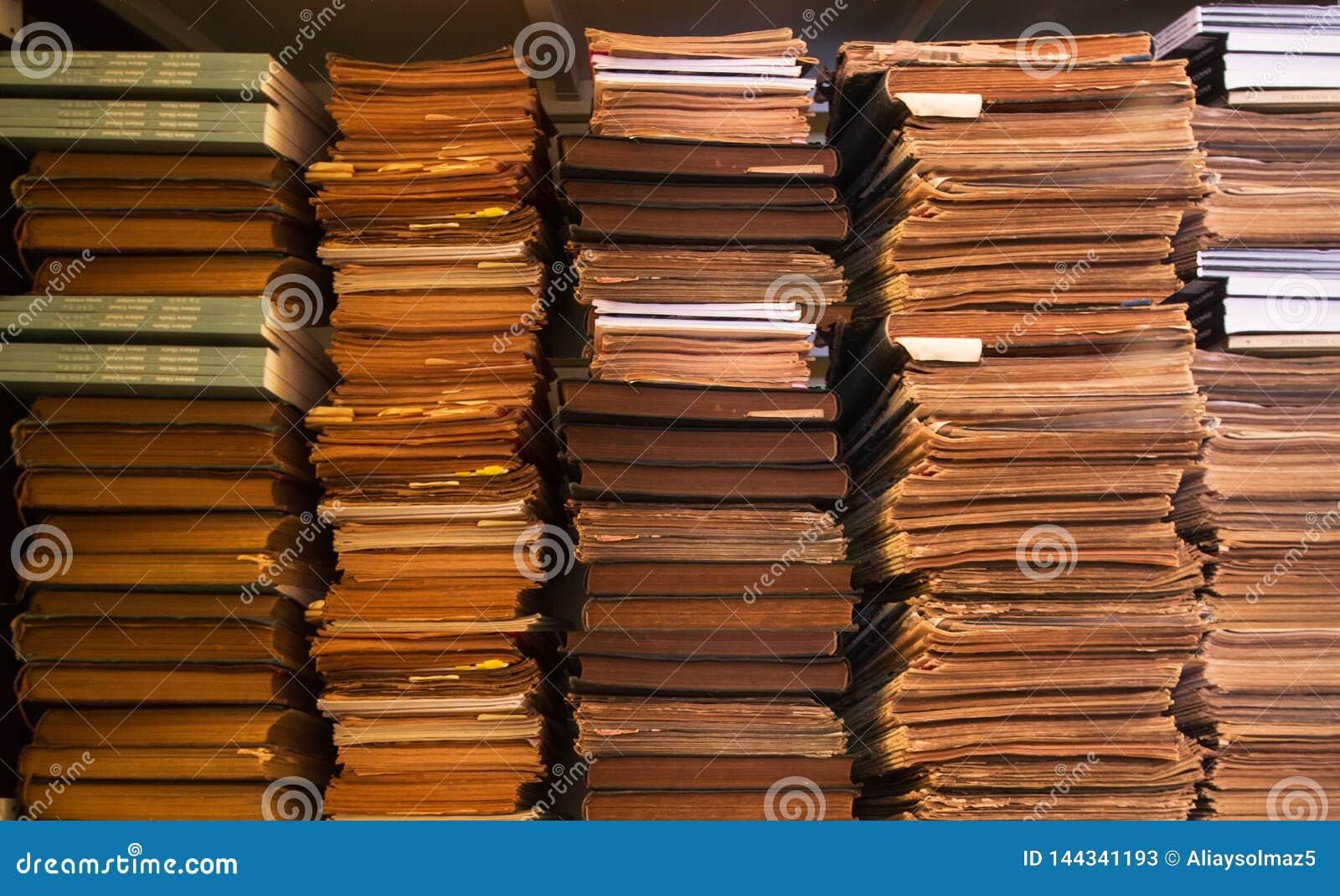 Старые античные книги на книжных полках, предпосылке книжных полков, стоге старых книг и бумагах