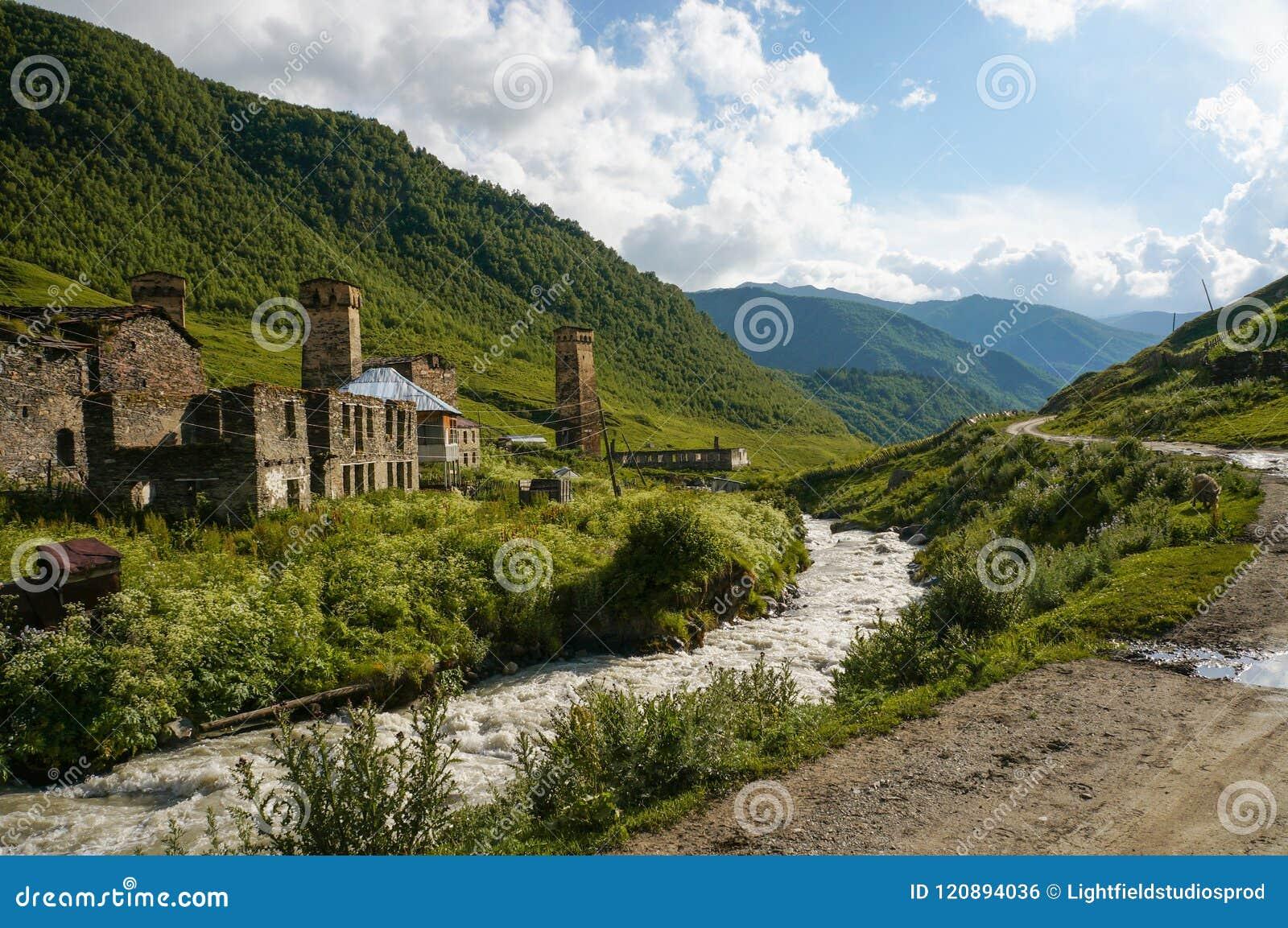 старые выдержанные здания против малого реки текут против холмов, Ushguli,