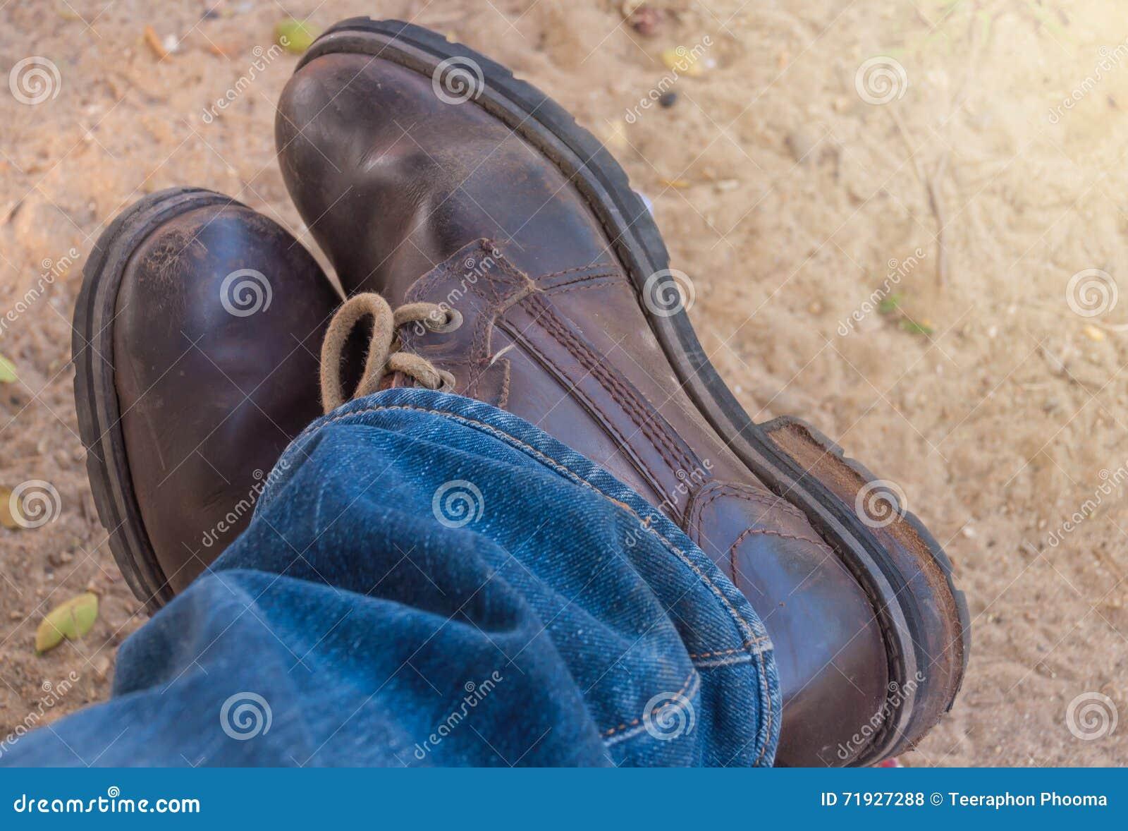 Старые голубые джинсы и коричневые ботинки