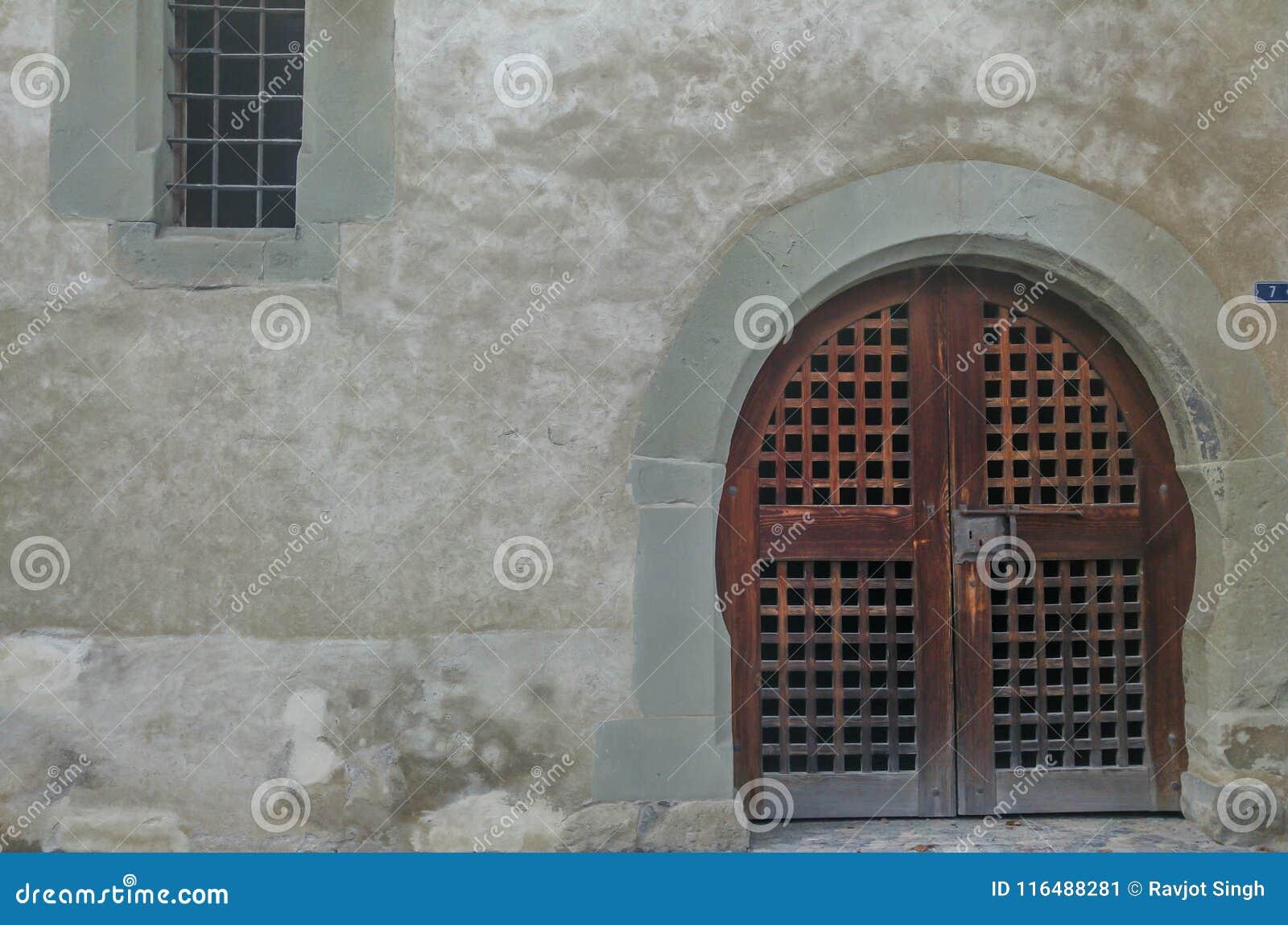 Старые деревянные закрытые дверь и окно с треснутой стеной в улицах деревни Lohara в Ludhiana, Пенджабе