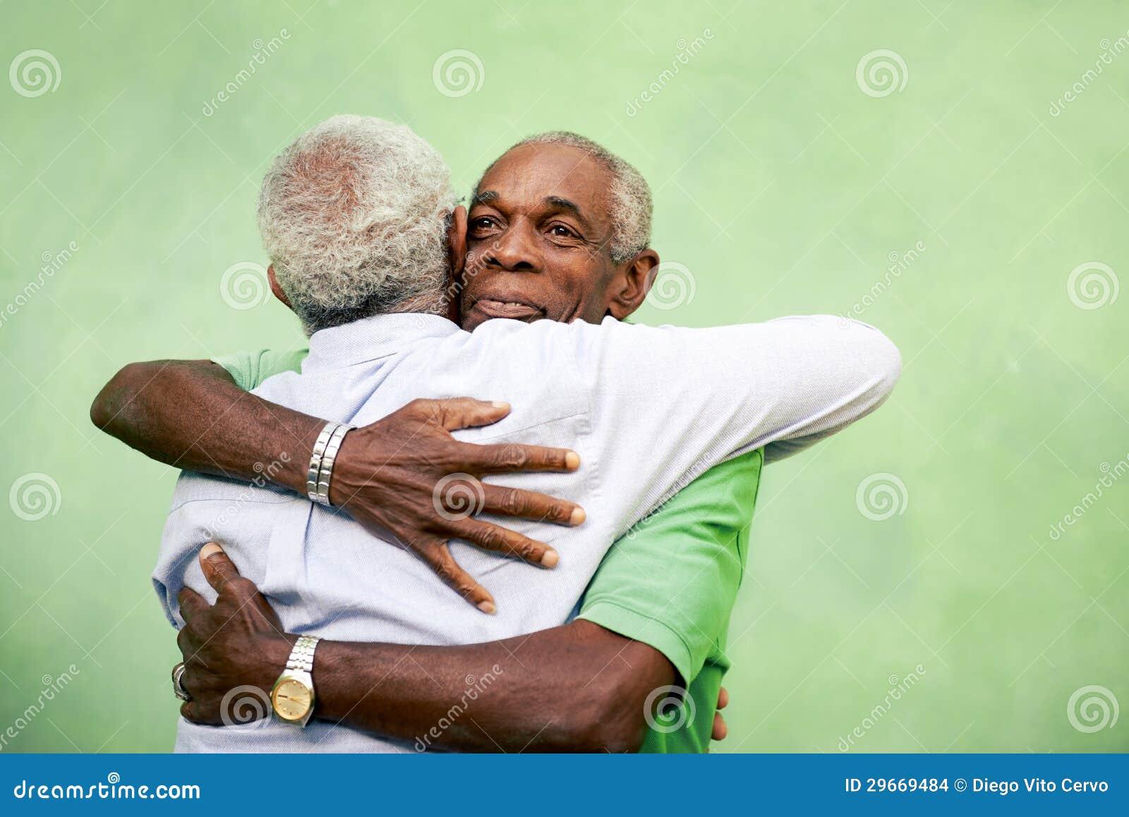Старые други, 2 старших люд афроамериканца встречая и обнимая